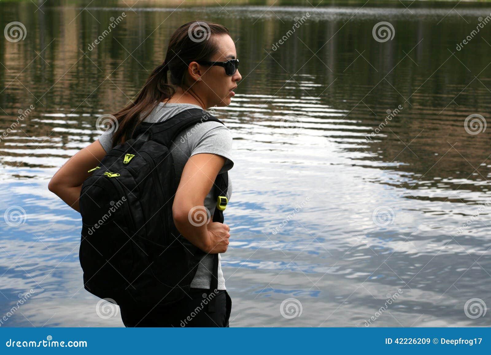 Fotvandraren i bergen vilar på en sjö