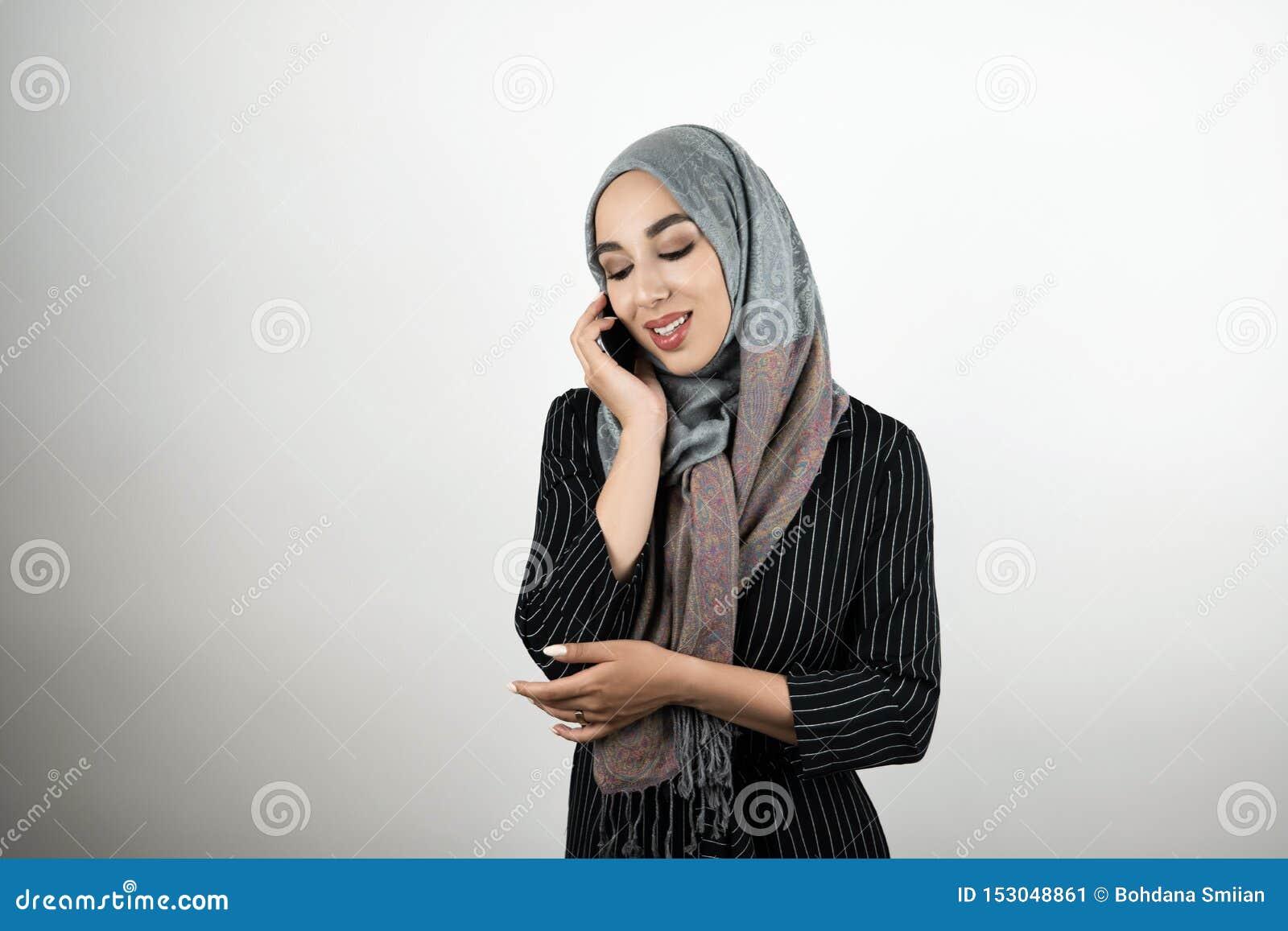 Foulard d uso del hijab del turbante della giovane bella donna musulmana felice che parla sui precedenti bianchi isolati smartpho