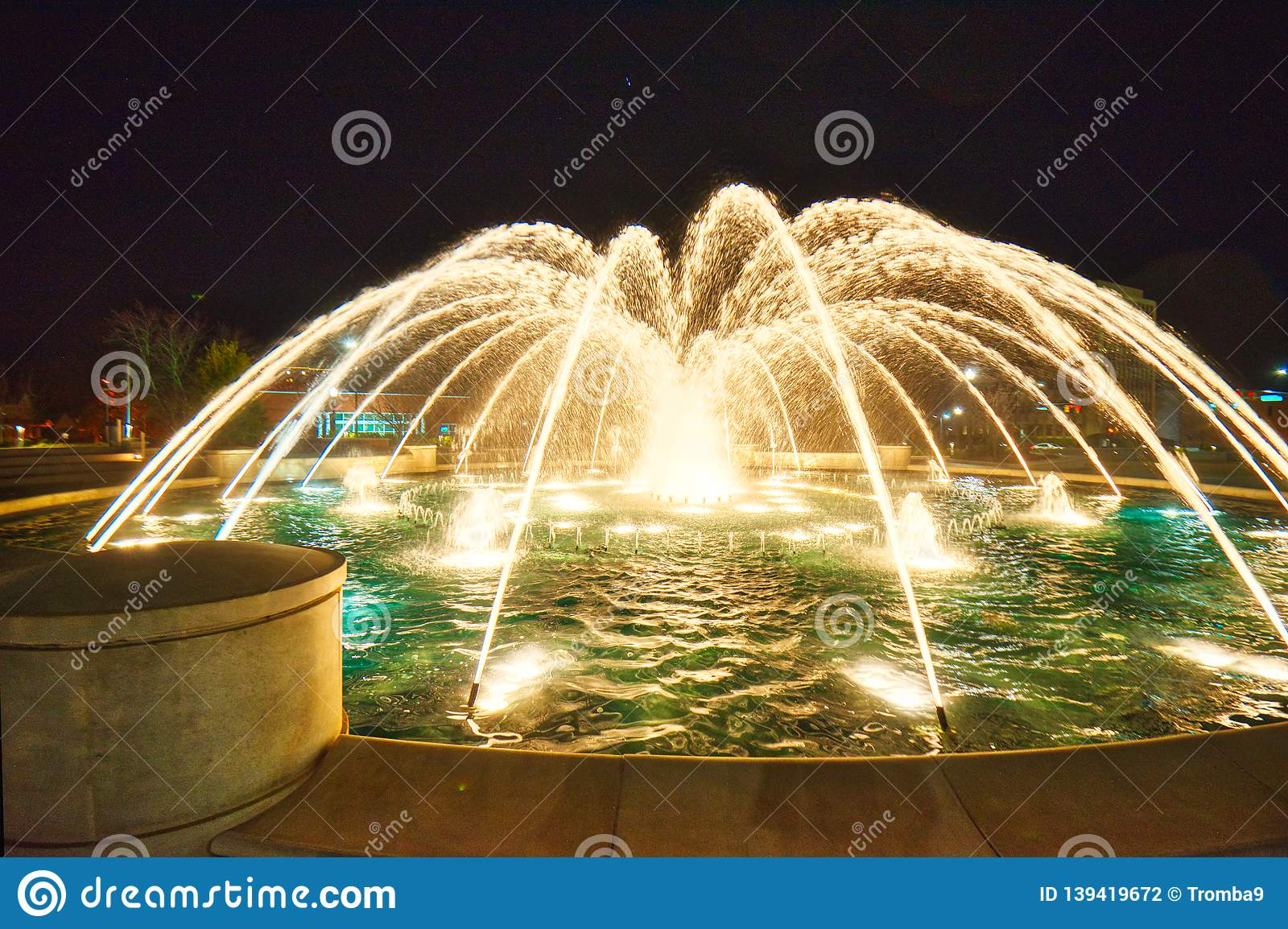 A composite image of 5 different exposures of a fountain at night.