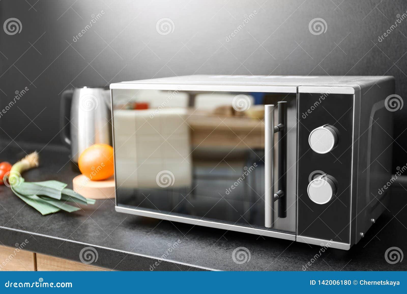 Etagere Dessus Micro Onde four à micro-ondes et ingrédients modernes sur la table