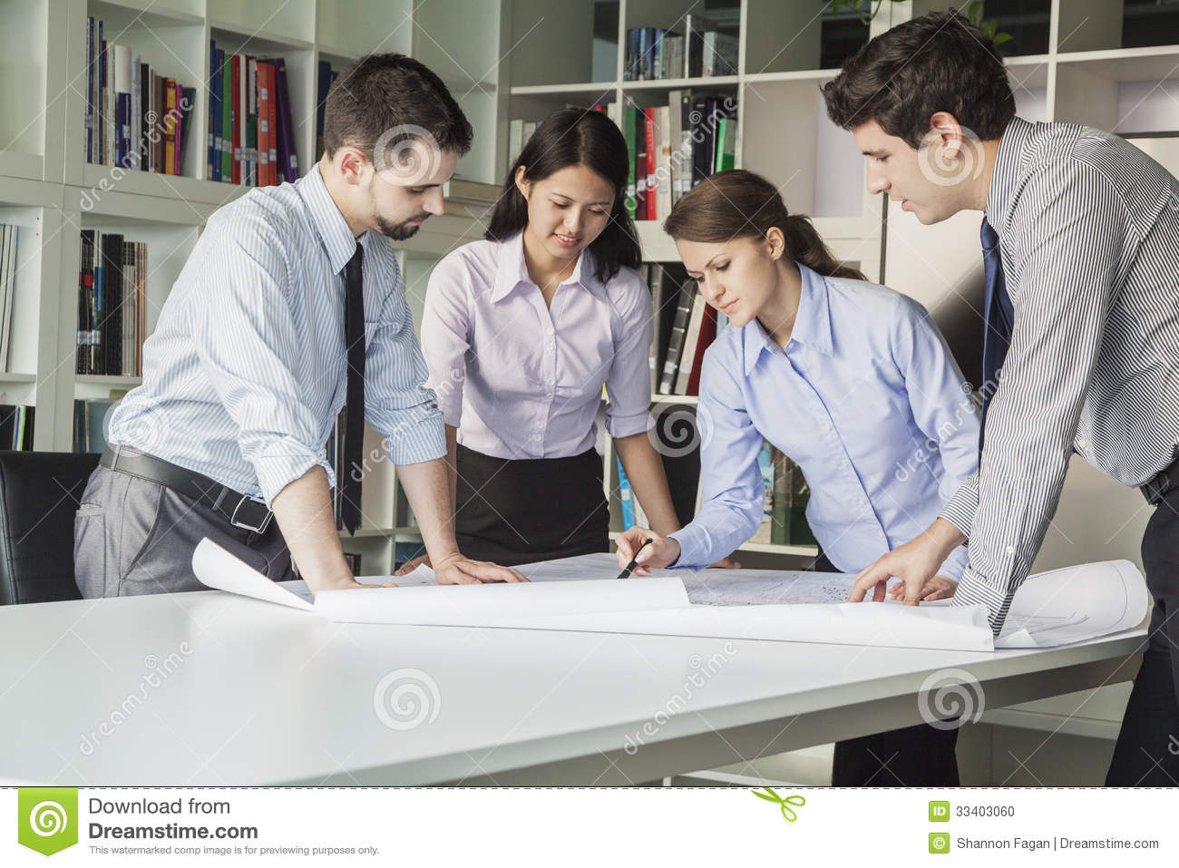 four architects standing and planning around a table while looking down at blueprint stock photo. Black Bedroom Furniture Sets. Home Design Ideas