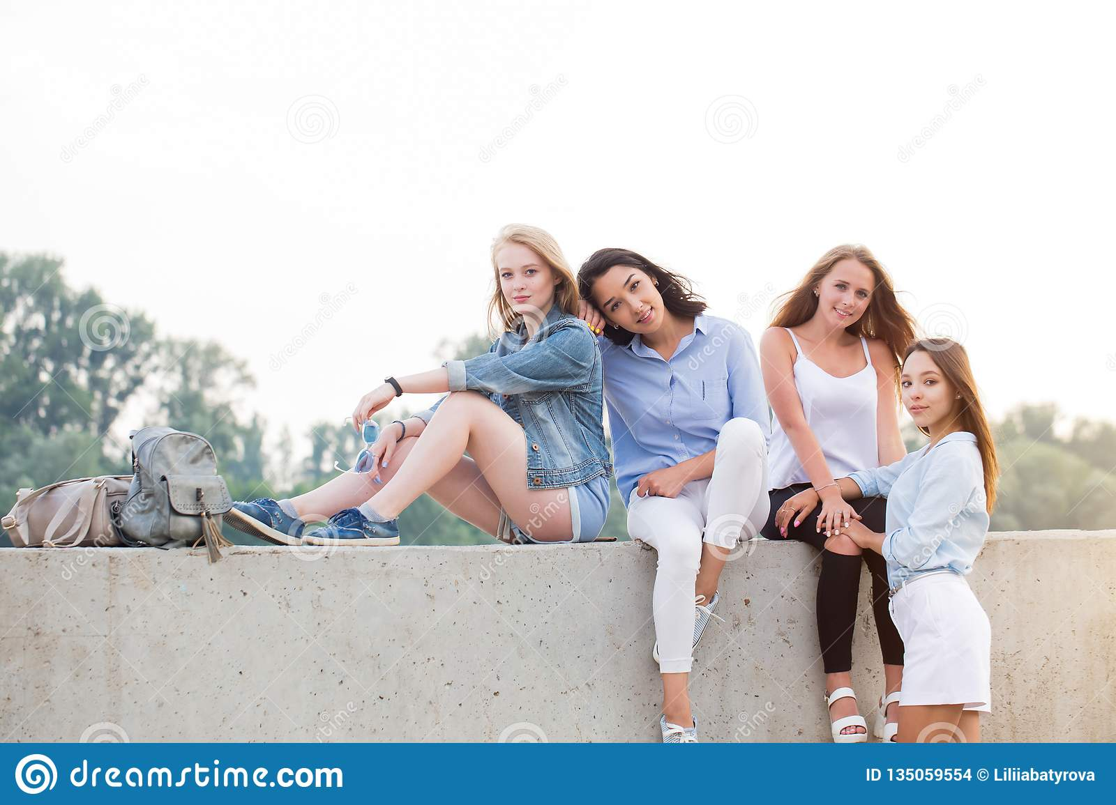 Four attractive female students posing outdoor while sitting in the Park, looking at camera