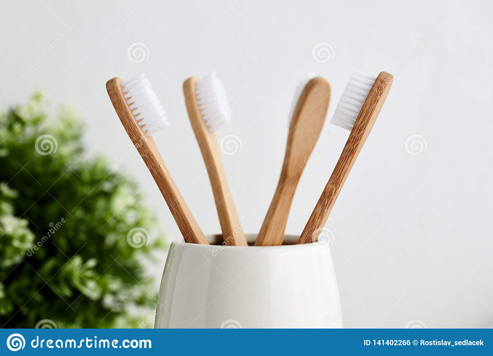 Four bamboo toothbrushes in gray glass