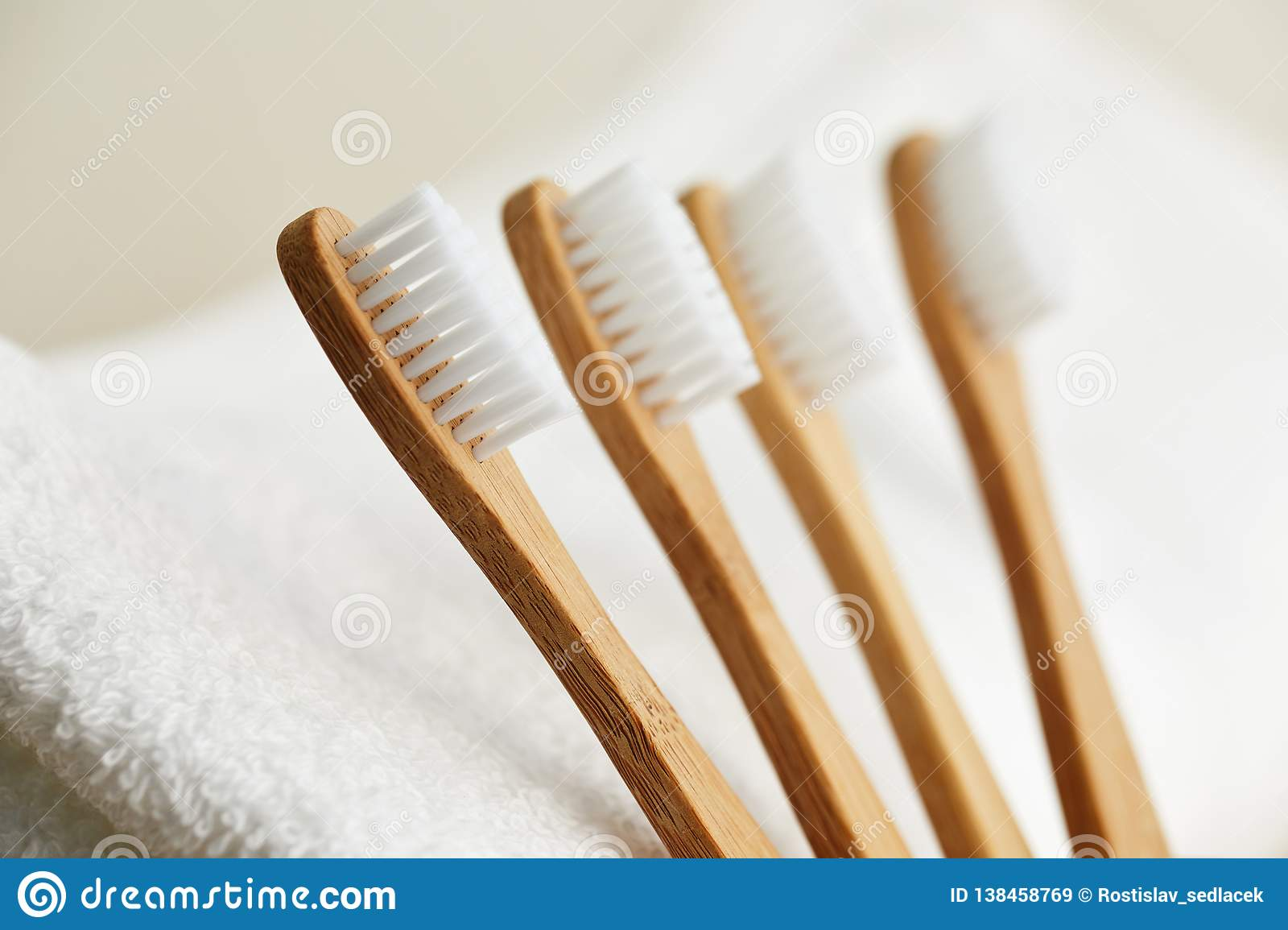 Four bamboo toothbrushes on white towel