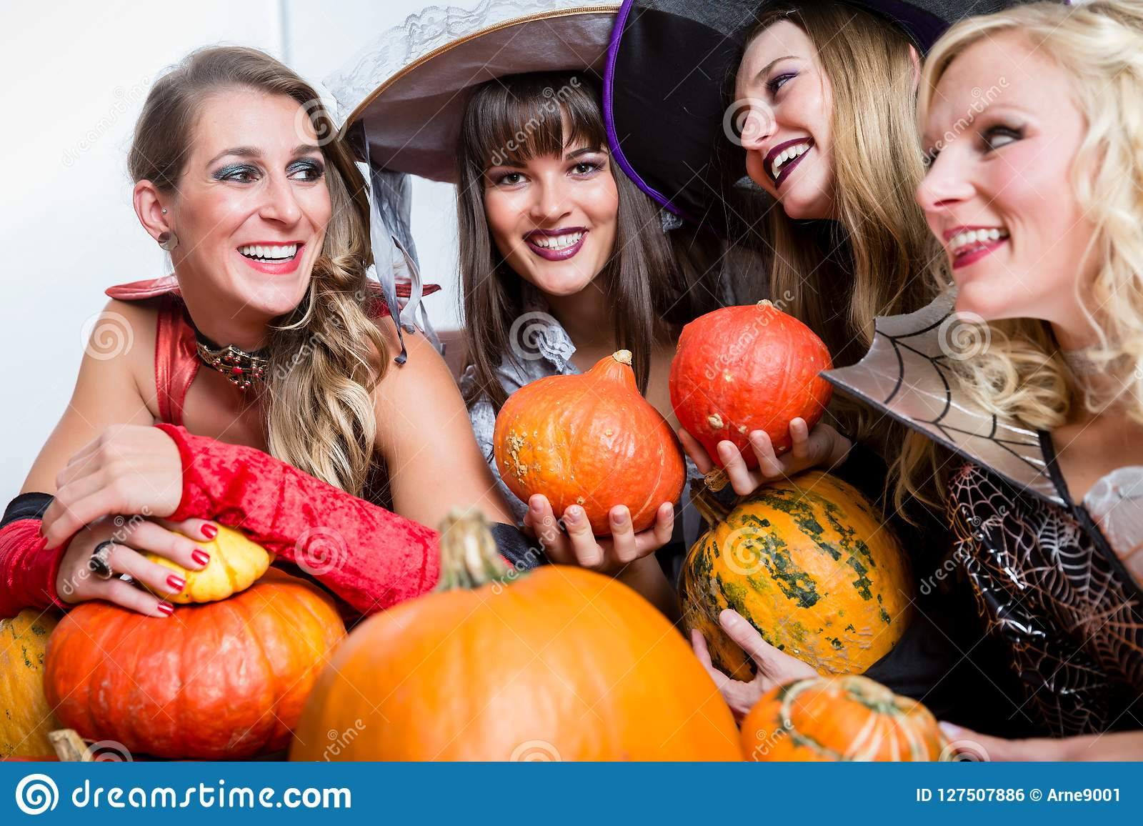 Four beautiful women acting as witches joining their malicious forces