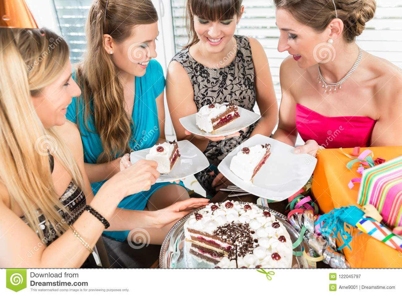 Four beautiful women and best friends smiling while sharing a birthday cake