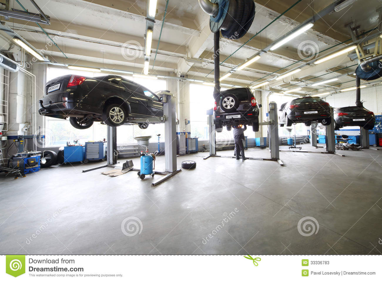 Four black cars on lifts in small service station stock for Design moderno garage per auto