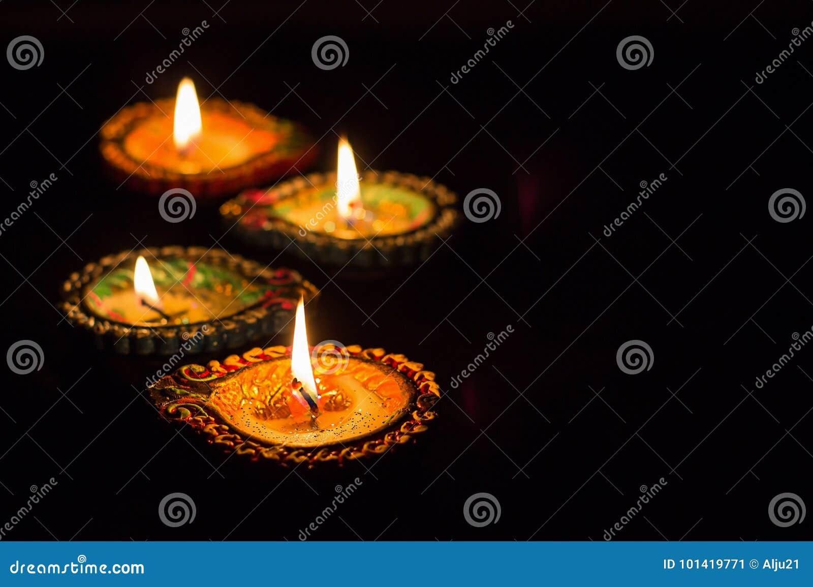 Four burning colorful clay diya lamp Diwali celebration. Black b
