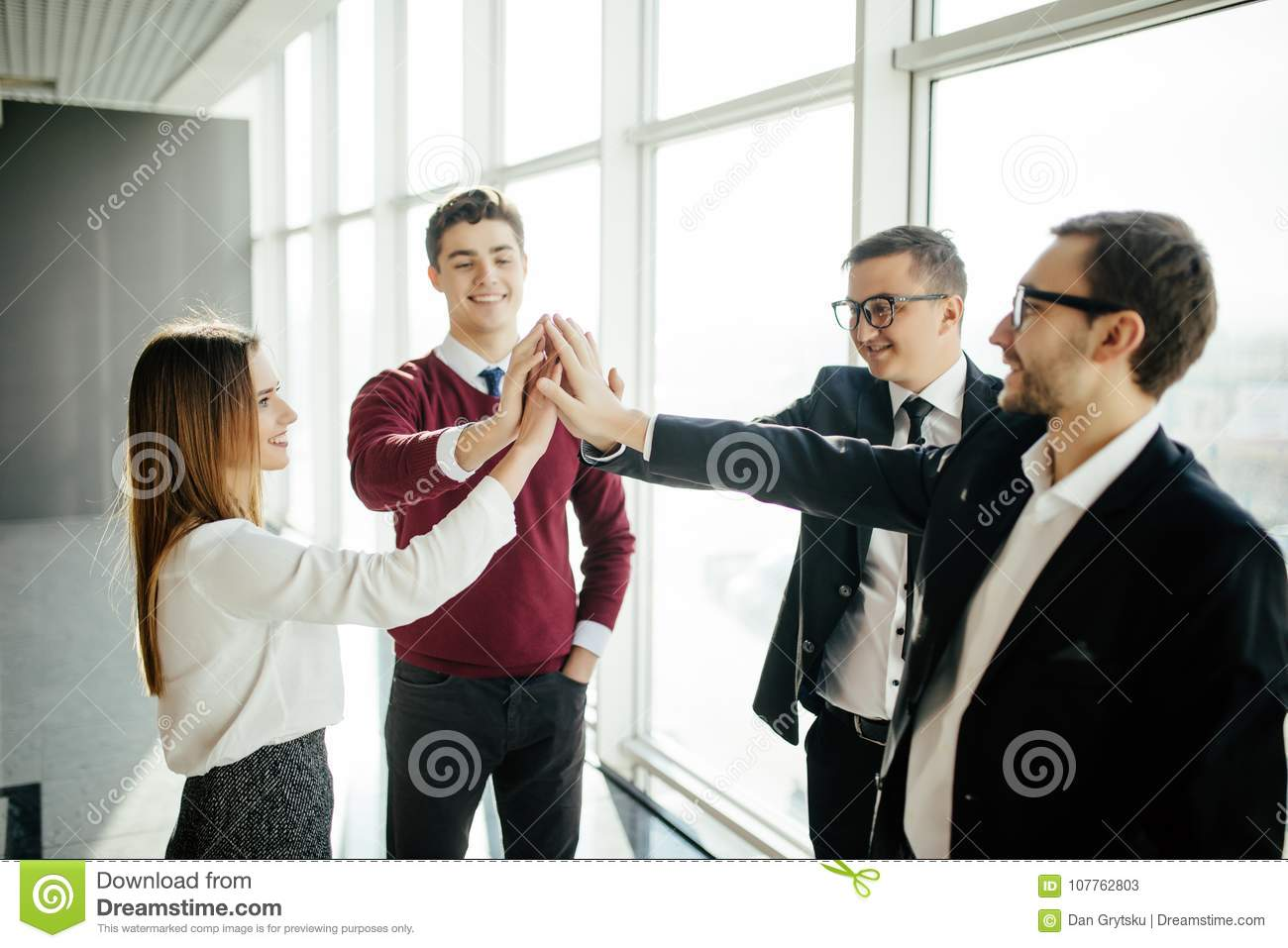 The four business people greeting with a high five against office download the four business people greeting with a high five against office background stock image m4hsunfo