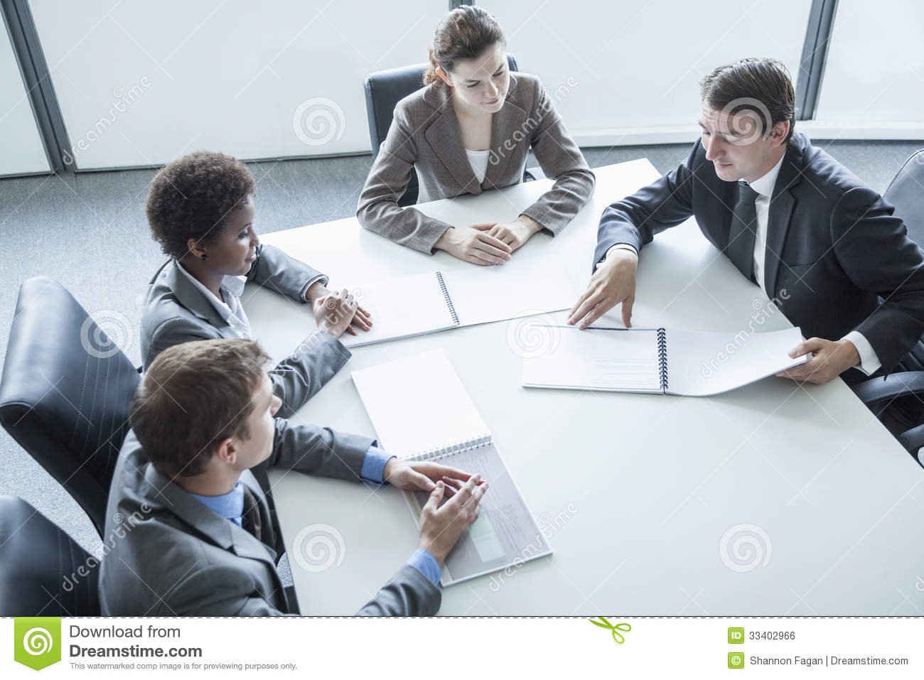 Four Business People Sitting Around A Table And Having A
