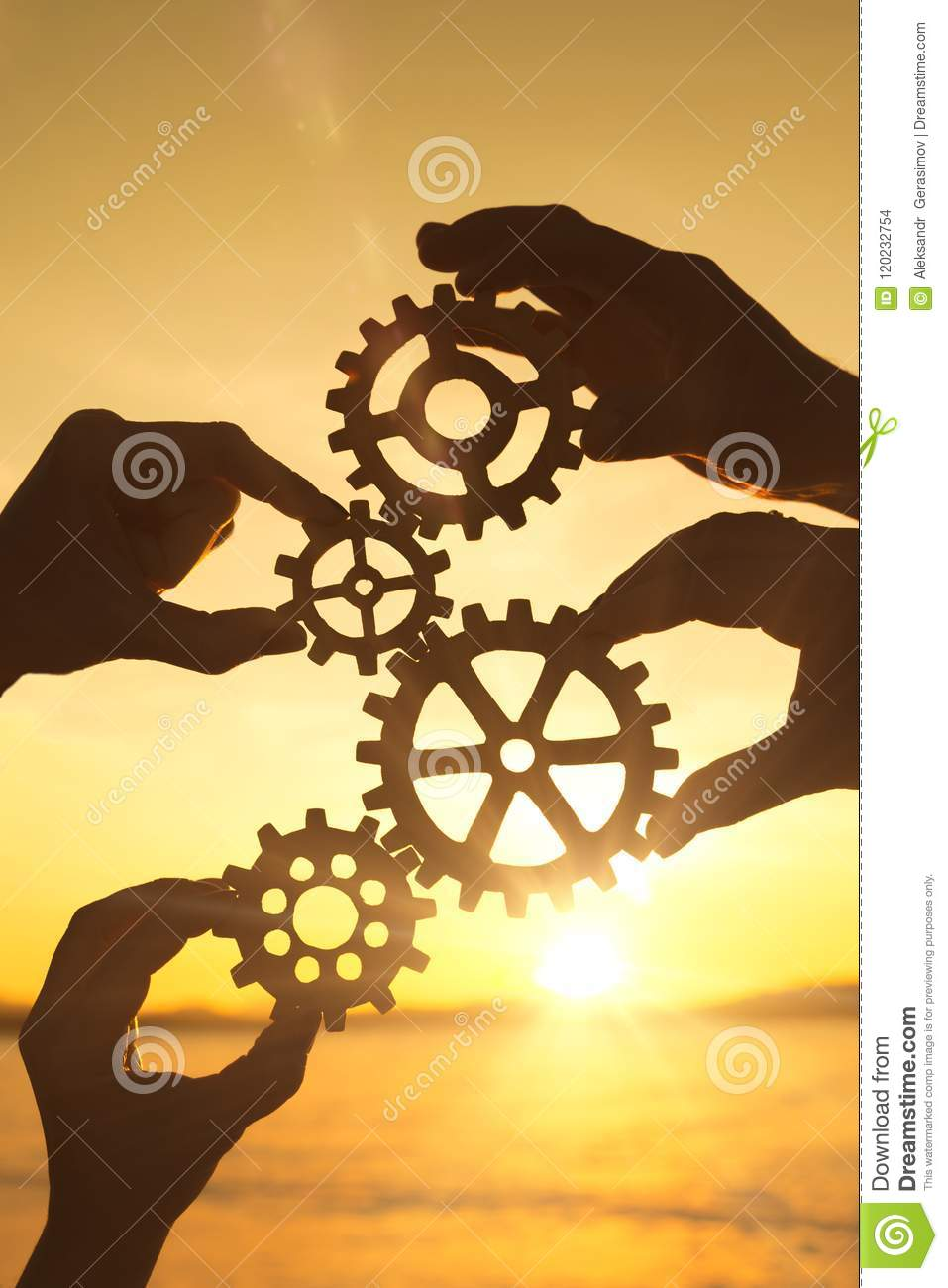 Four businessmen`s hands collect a puzzle of gears against the sunset.