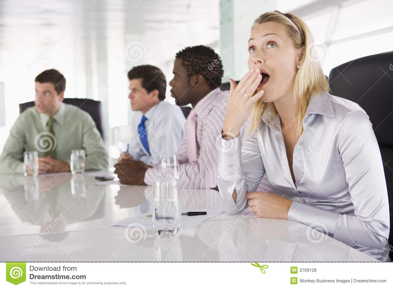 Four businesspeople in boardroom with one yawning