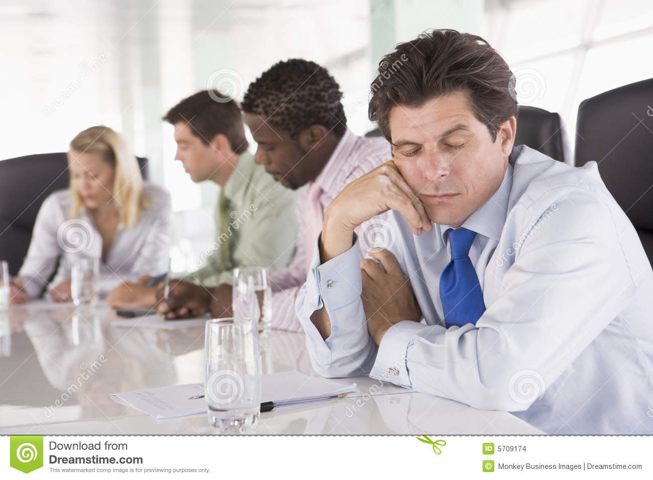 Four businesspeople in room with one man asleep