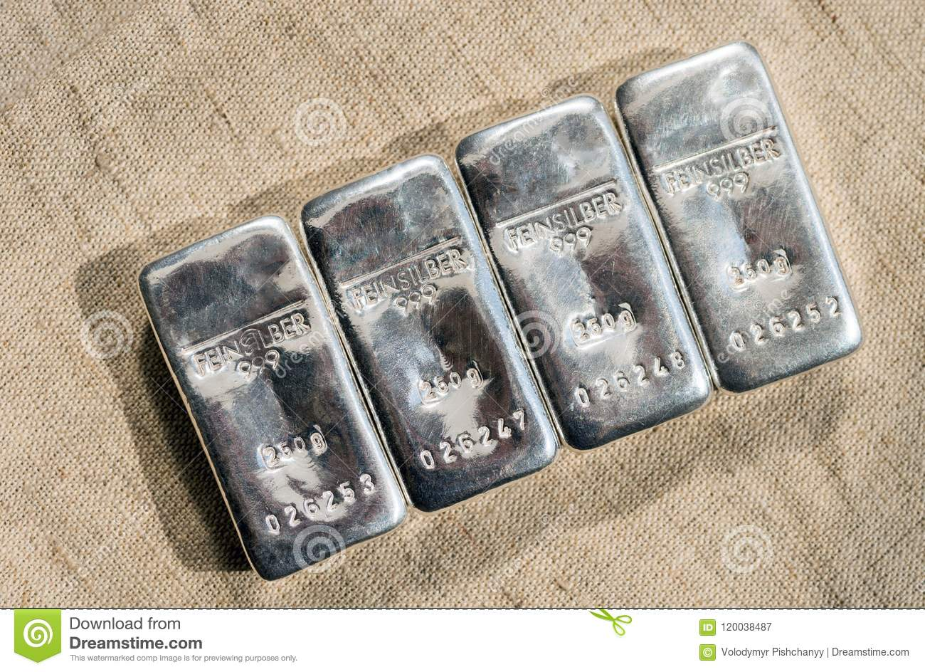 Four cast silver bars against the background of the texture of coarse cloth