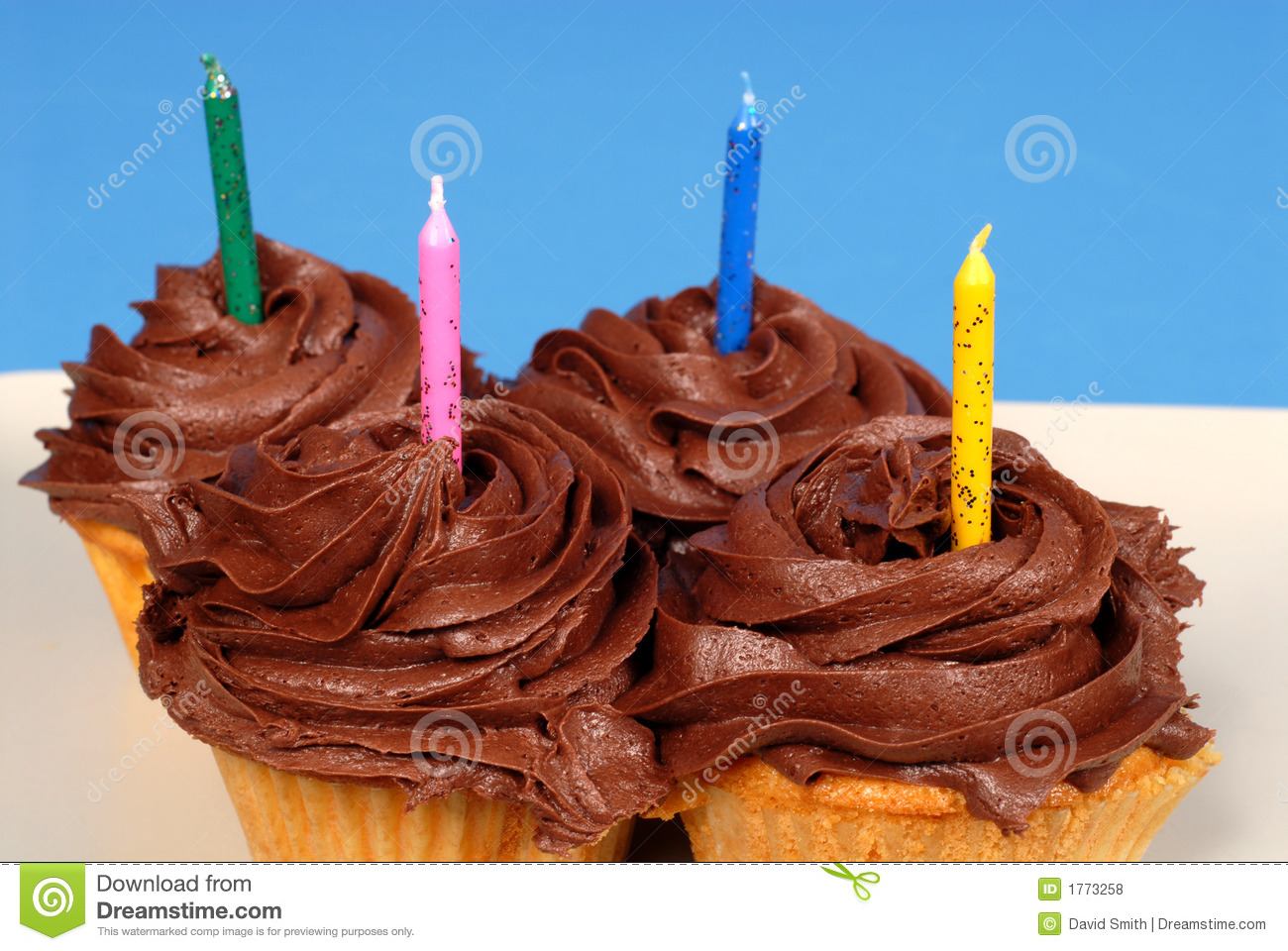 Four Chocolate Frosted Cupcakes With Candles Royalty Free ...