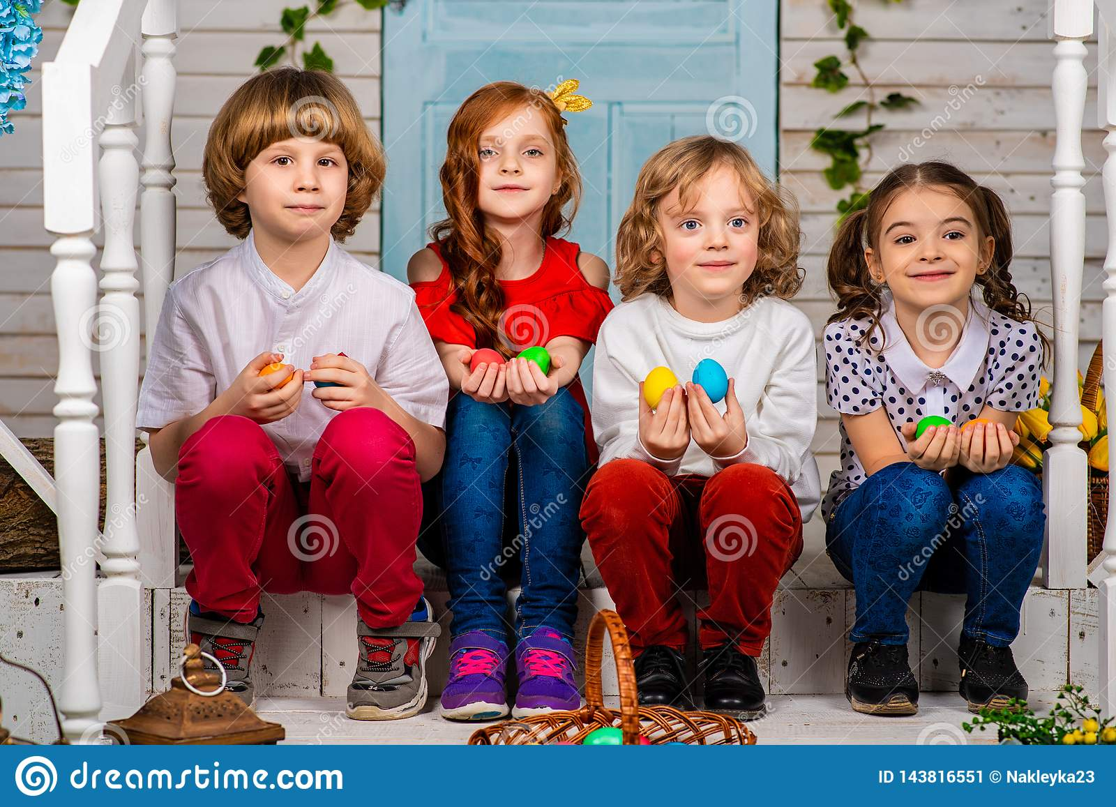 Four beautiful children, two boys and two girls stand on a wooden threshold and laugh