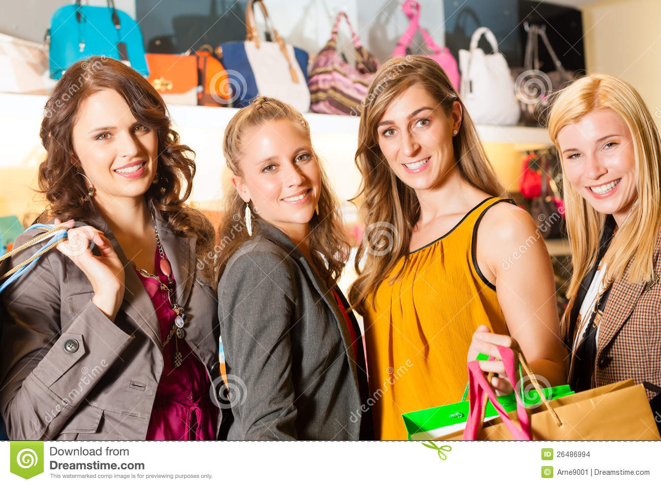 Four female friends shopping bags in a mall