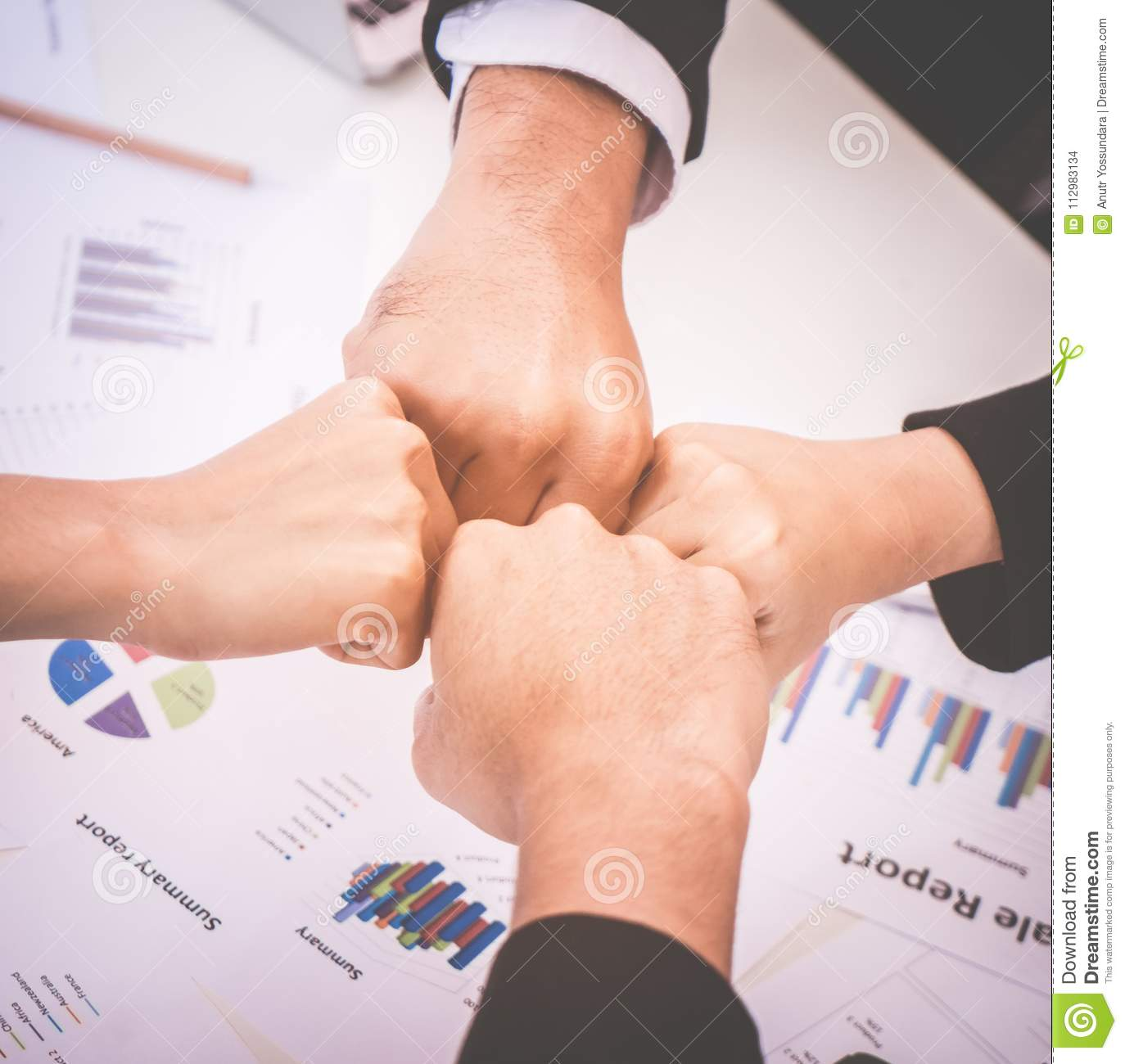 Fist bump in business meeting for team concept