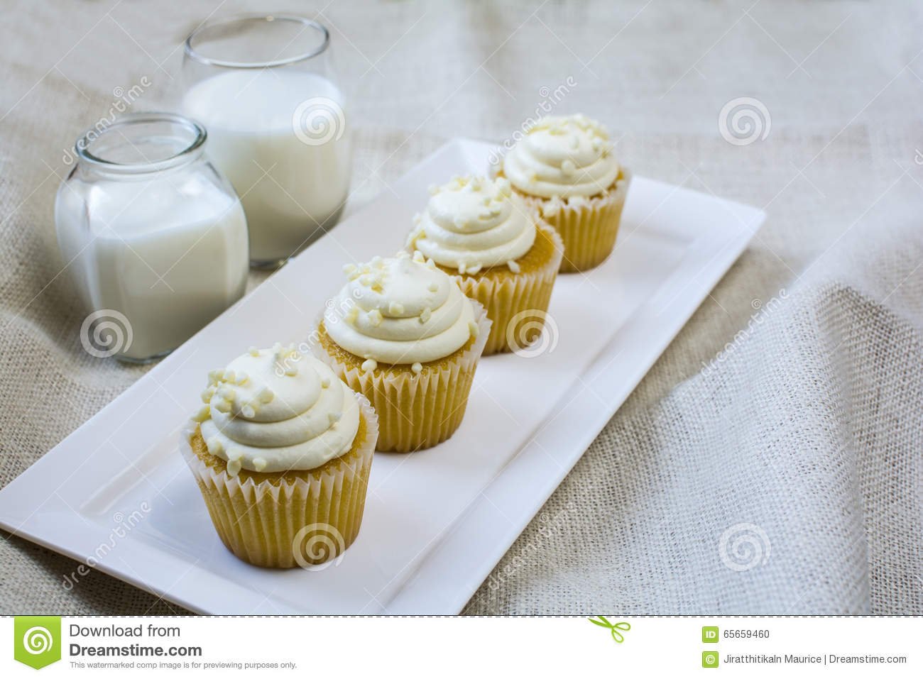 Four French Vanilla Cupcakes And Milk Glass Dessert Stock Photo
