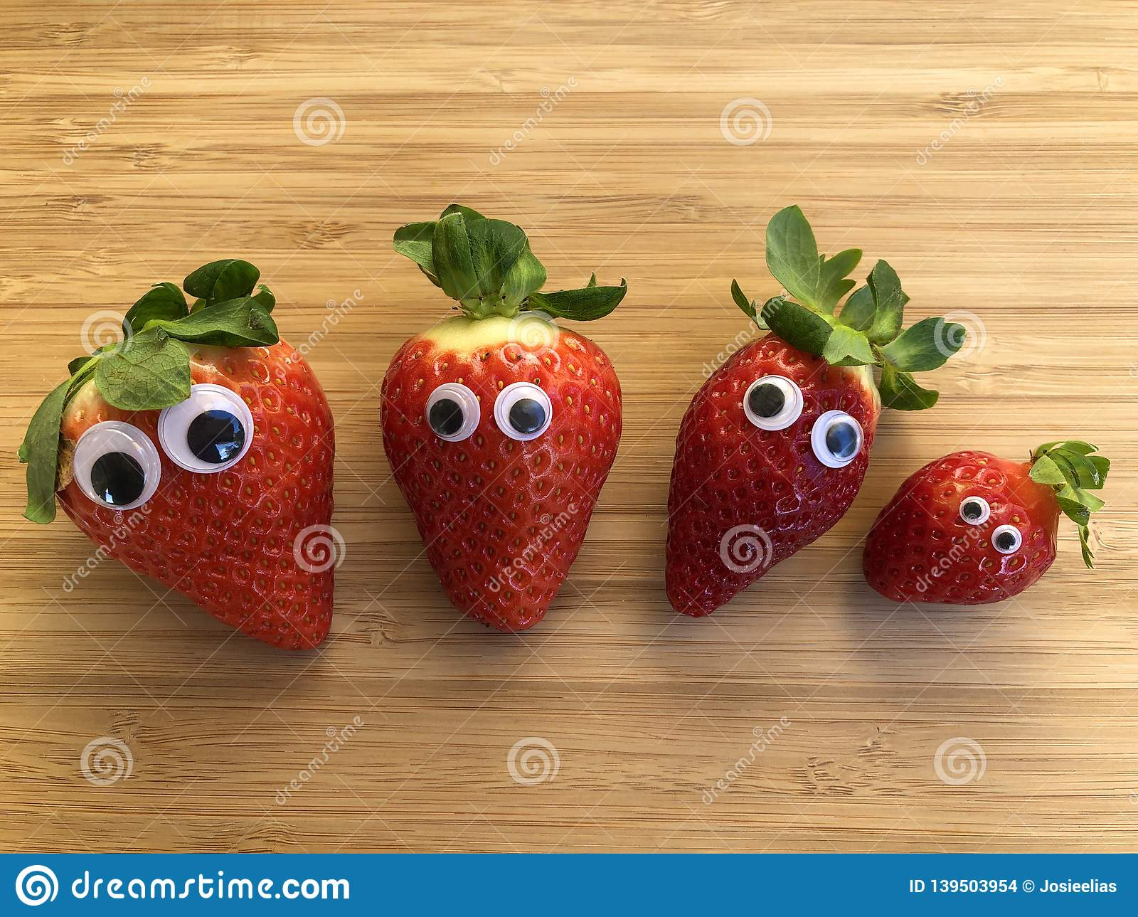Four fresh red strawberries with googly eyes