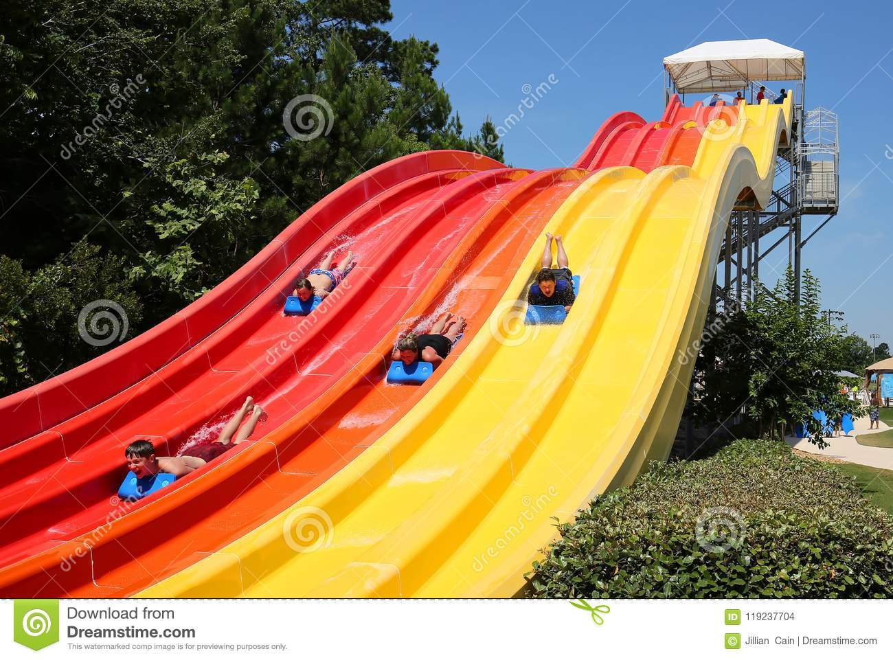 Four Friends Come Down The Big Water Slide Editorial Stock Image