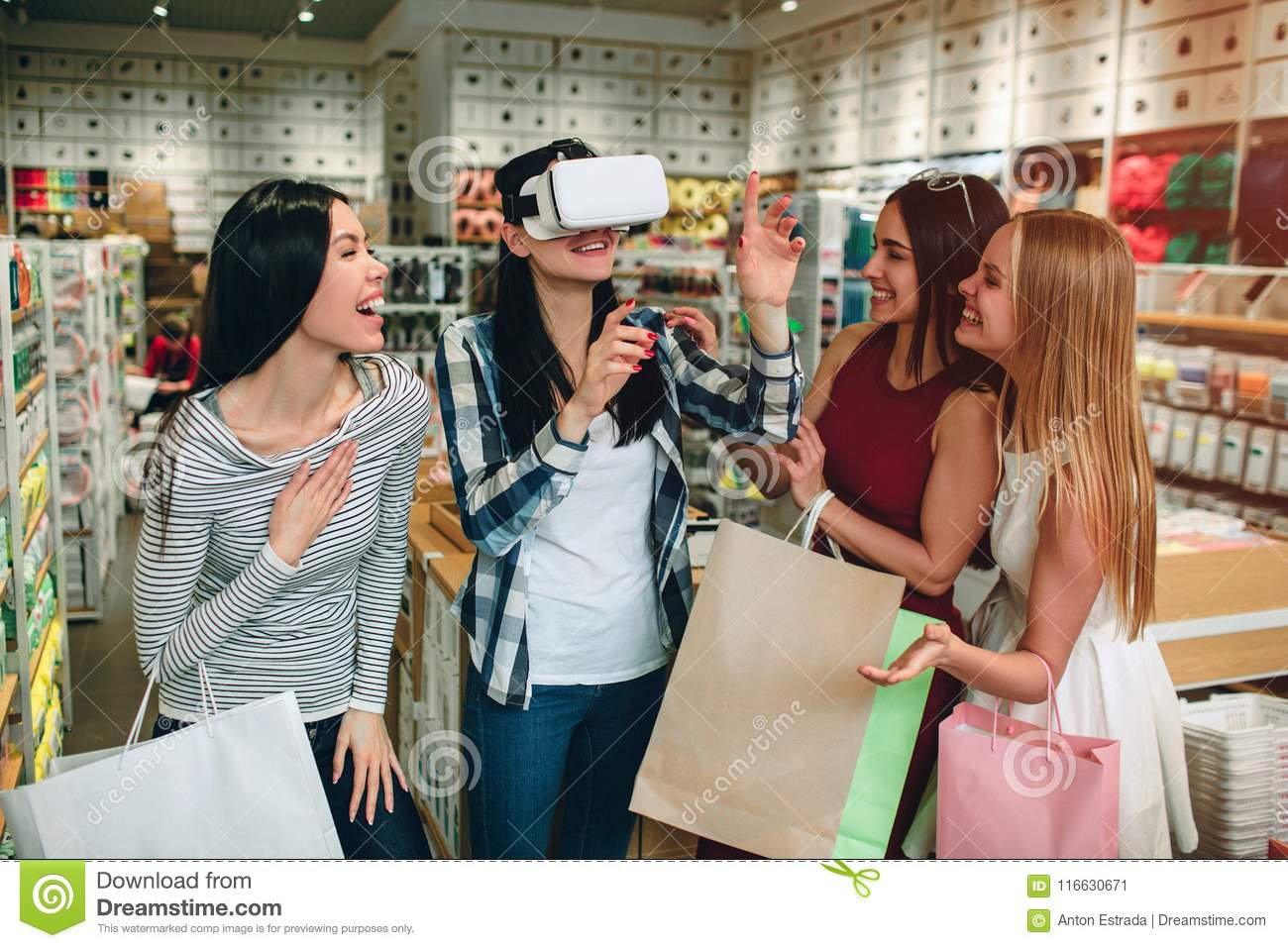 Four girls are having some fun. Brunette in shirt has VR glasses on her face and keeping her hands in the air while her