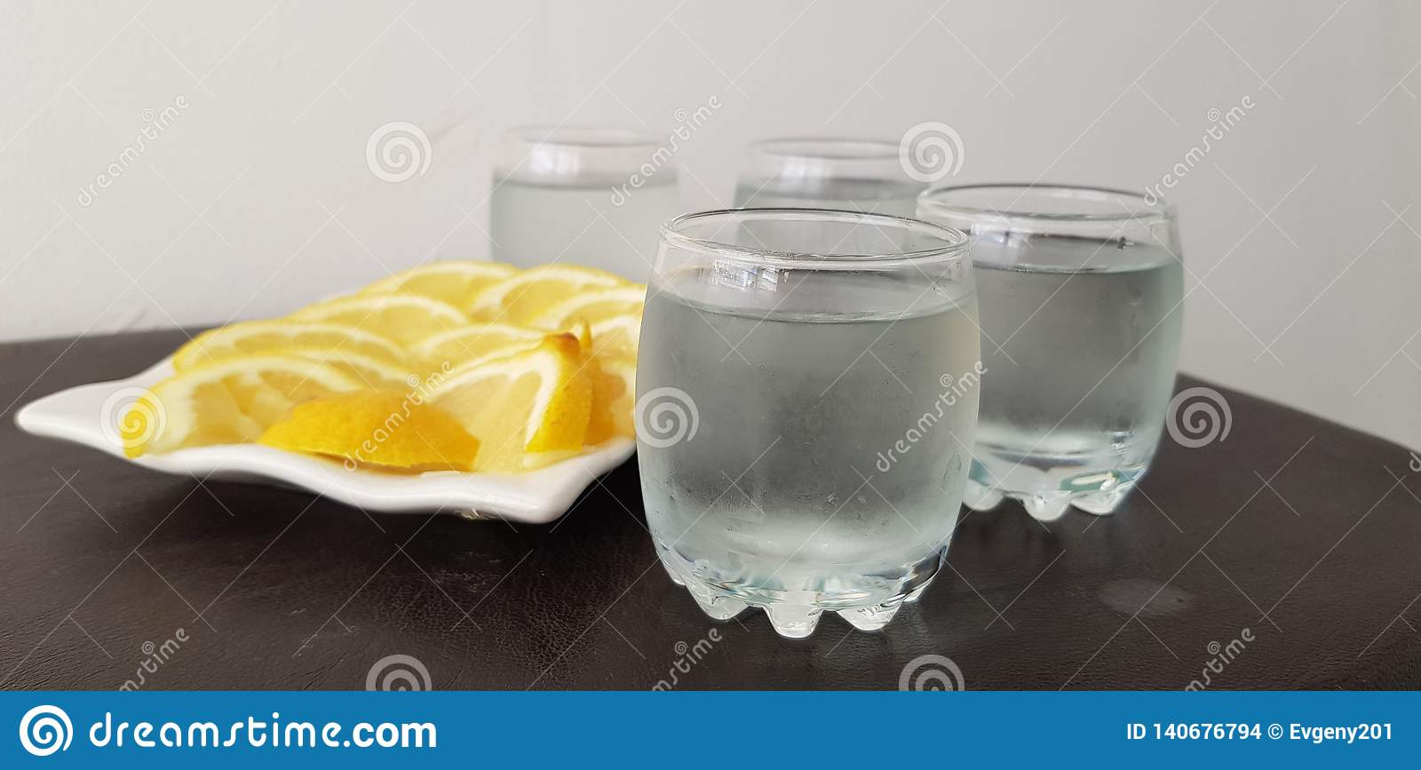 Four glasses with vodka with lemon