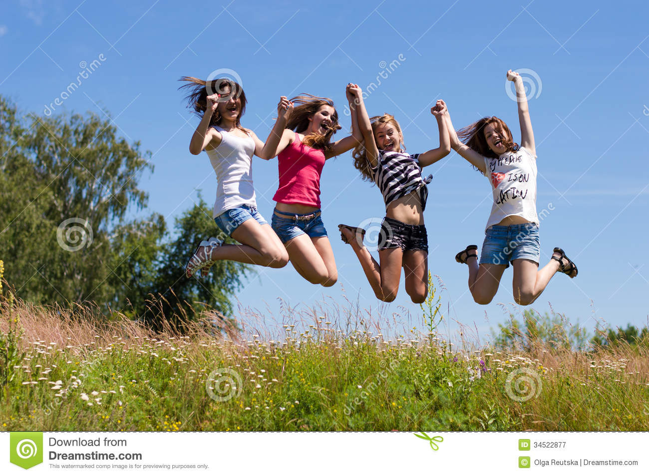 Four happy teen girls friends jumping high against blue sky