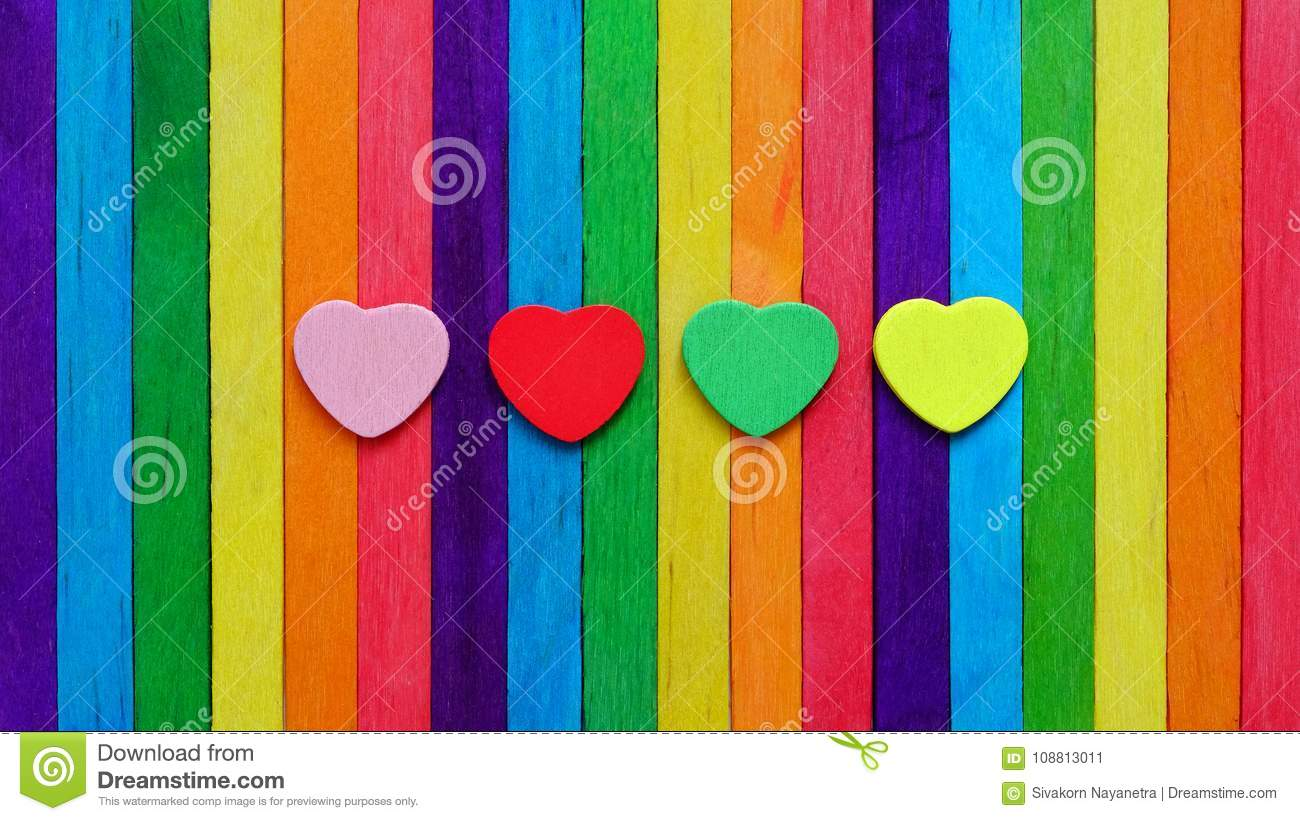 Four hearts in multiple colors on colorful ice-cream sticks line up as rainbow flag.