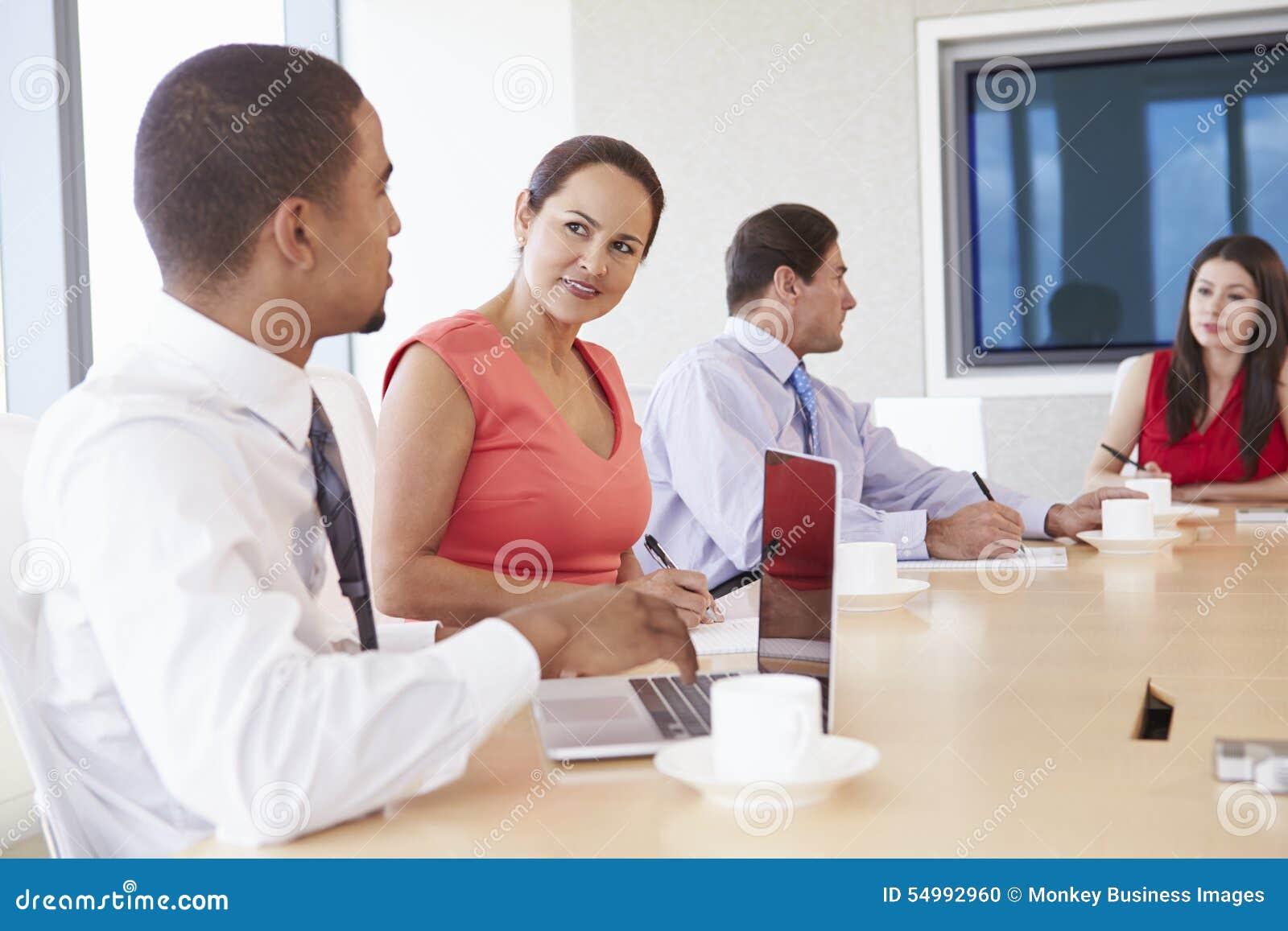 Four Hispanic Businesspeople Having Meeting In Boardroom