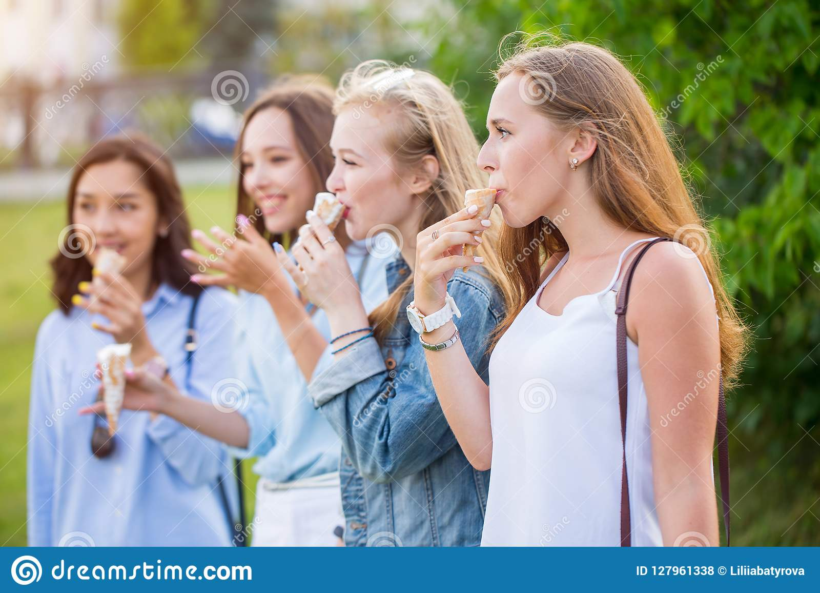 Four joyful young girlfriends standing in a row smiling happily eating ice cream in Park