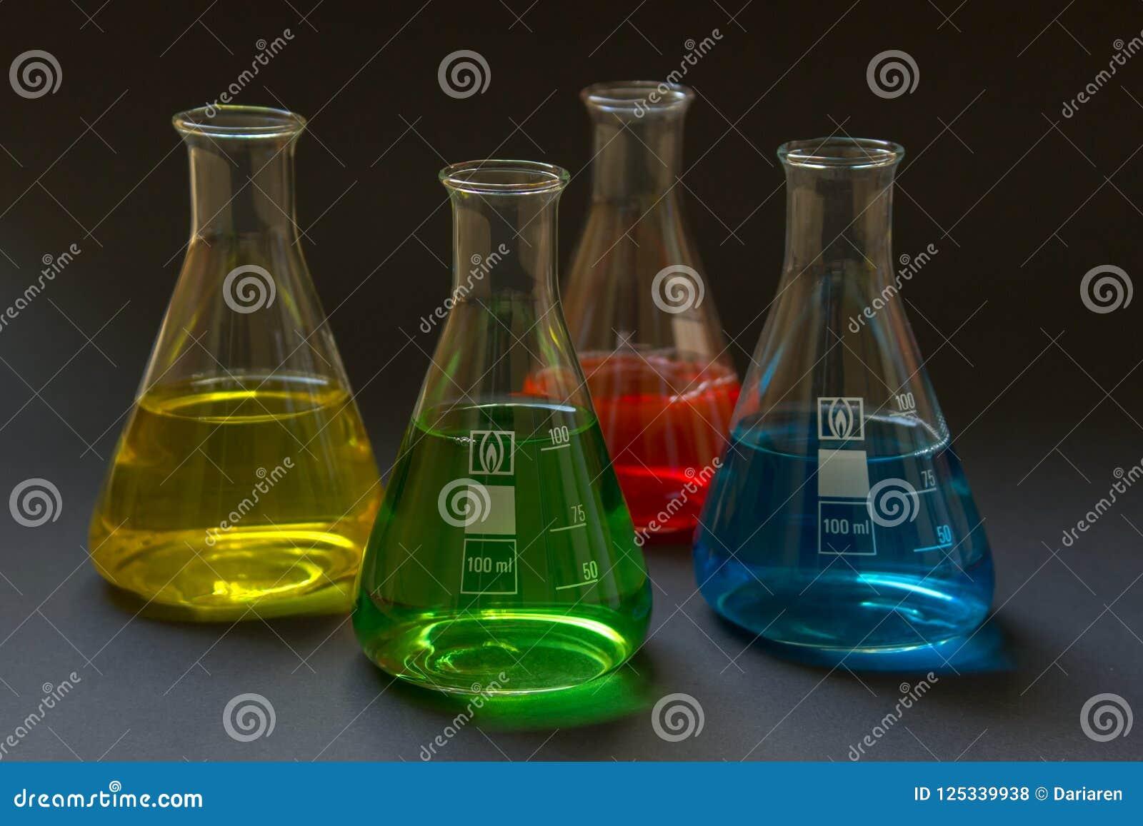 Four laboratory flasks with liquids.