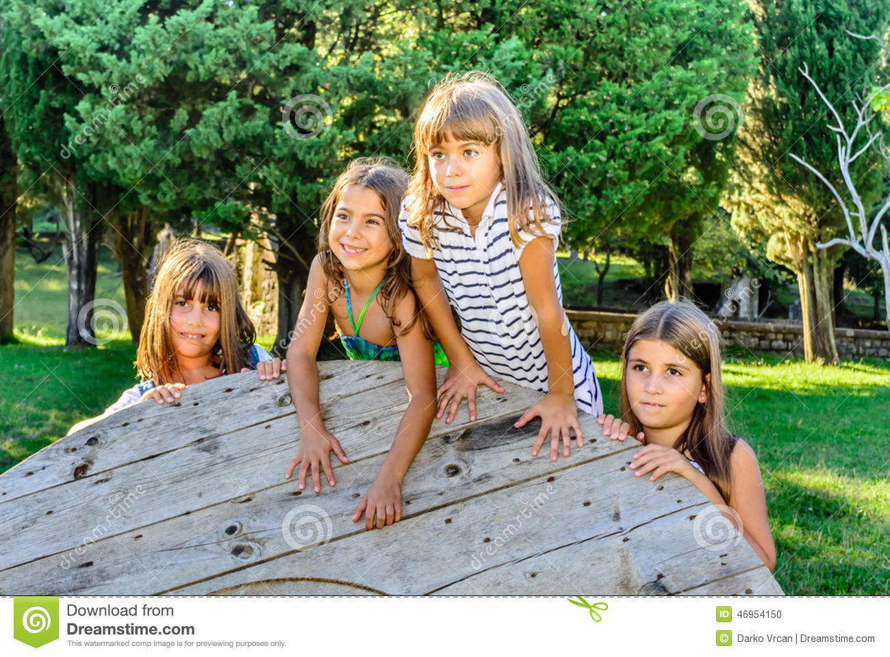 four little girls playing in the park stock photo