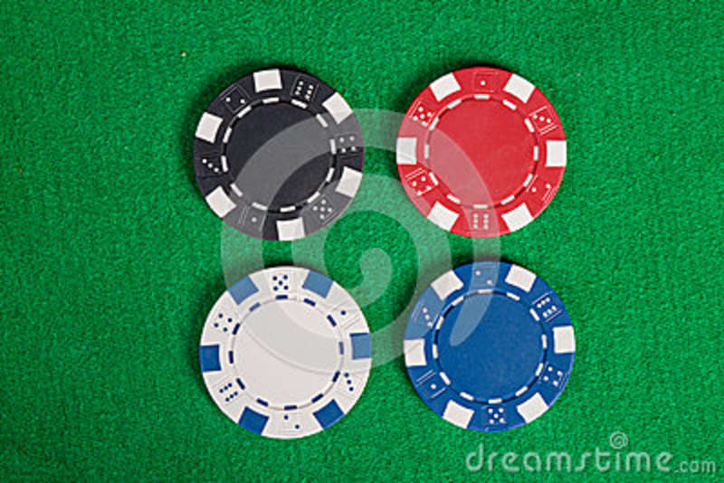 Four macro poker chips on green table