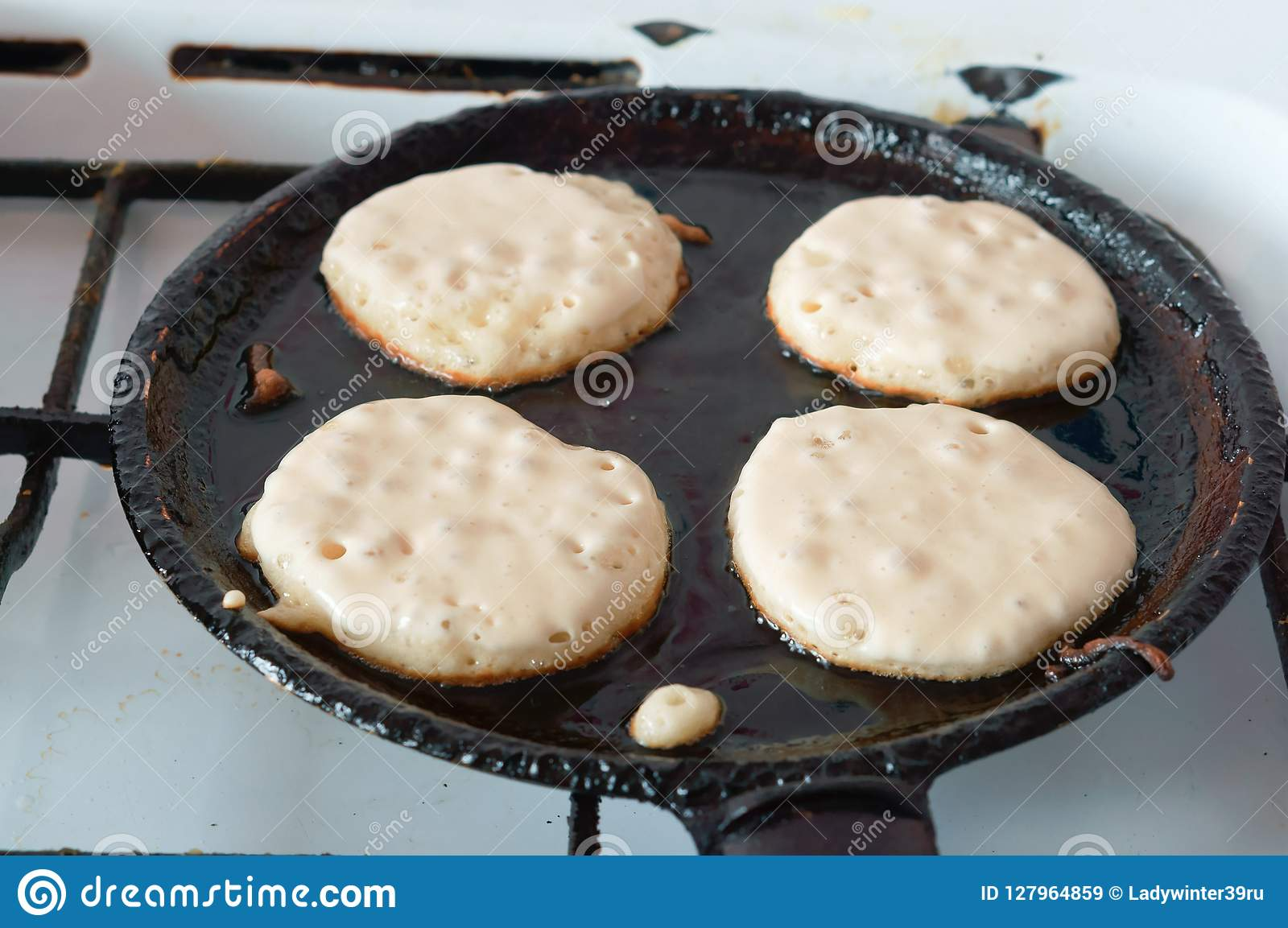 Four pancakes fried in a pan, cooking pancakes in a pan