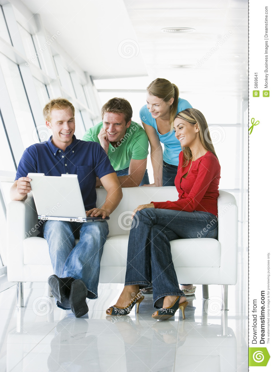 Four people in lobby looking at laptop smiling