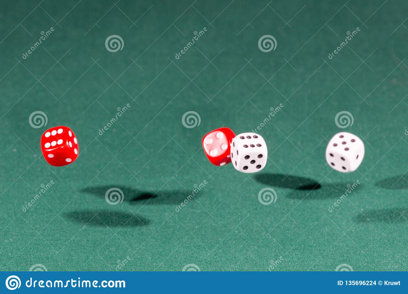 Four red and white dices falling on a green table