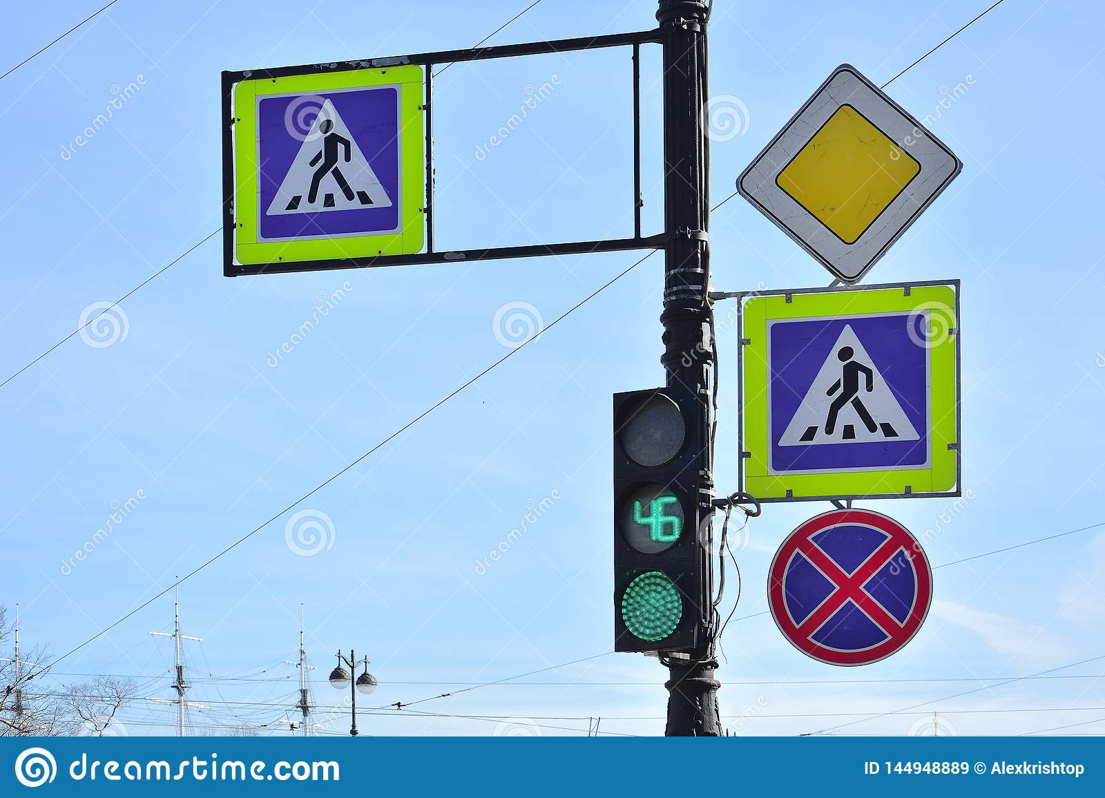 Four road signs and green traffic lightagainst blue background, Saint-Petersburg, Russia