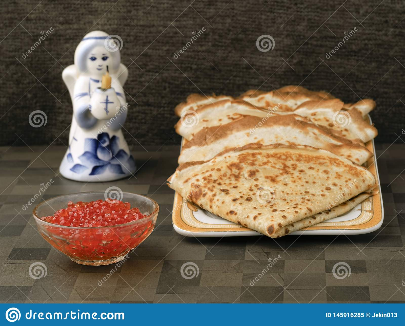 Four ruddy pancake neatly on the plate bowl with red caviar. Next figure of an angel holding a Church candle