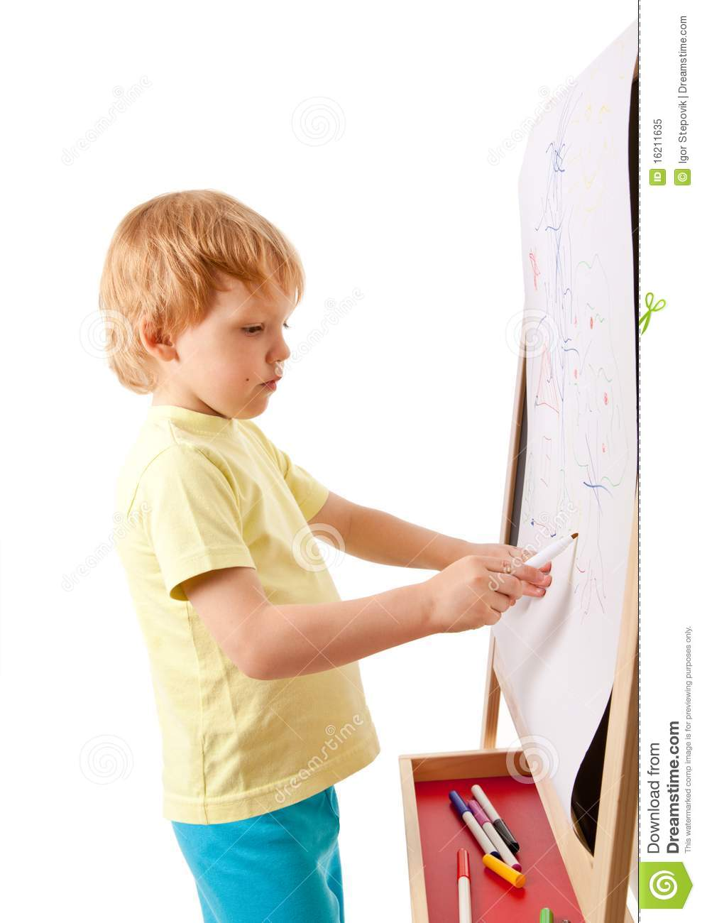 Four-year old boy drawing picture on easel