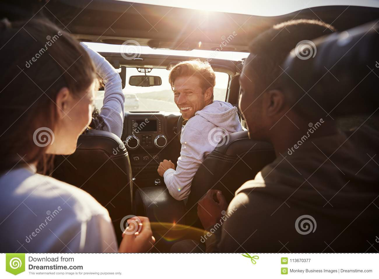 Four young adult friends together in a car on a road trip