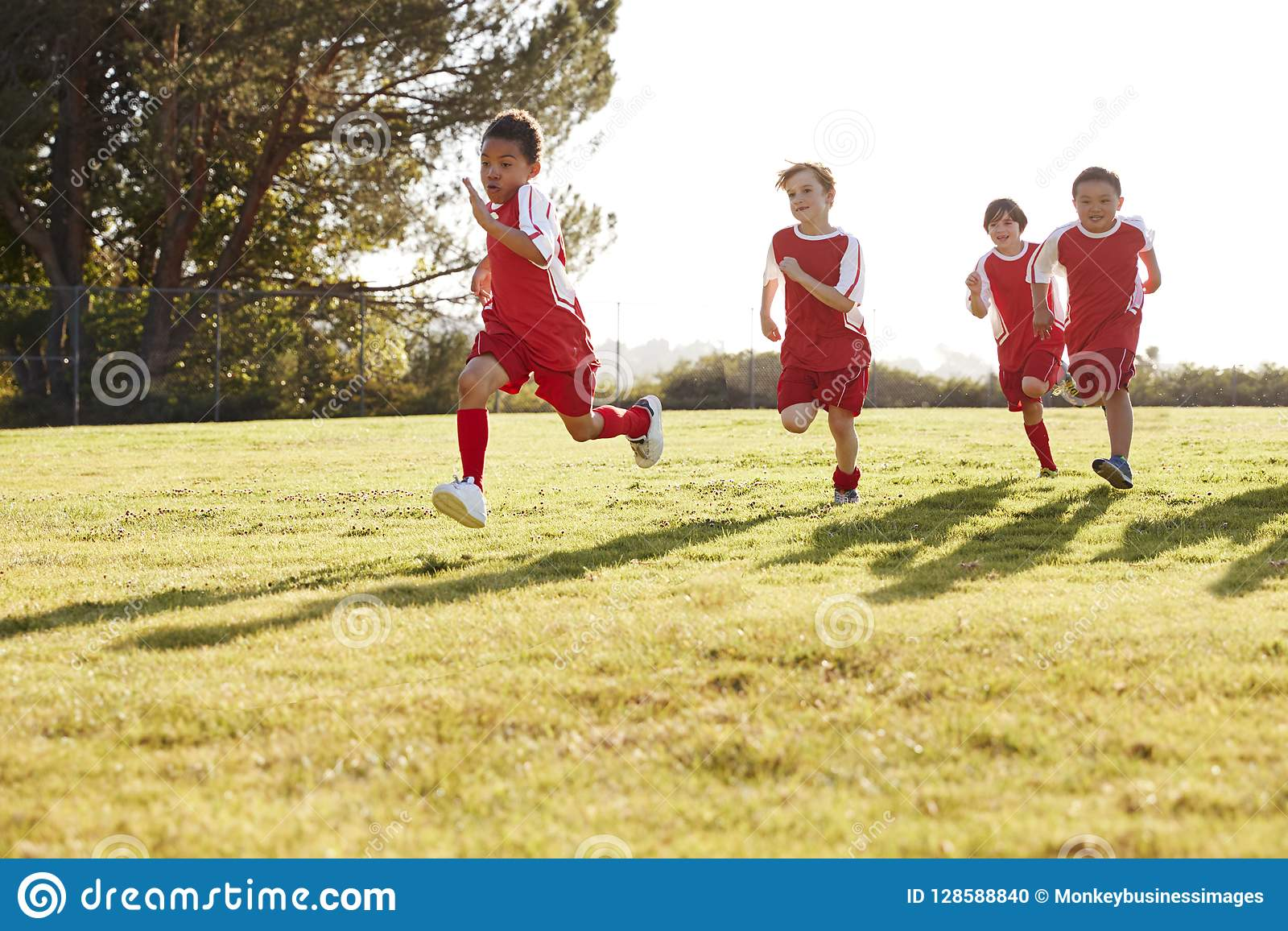 Four young boys in football strip running in a playing field