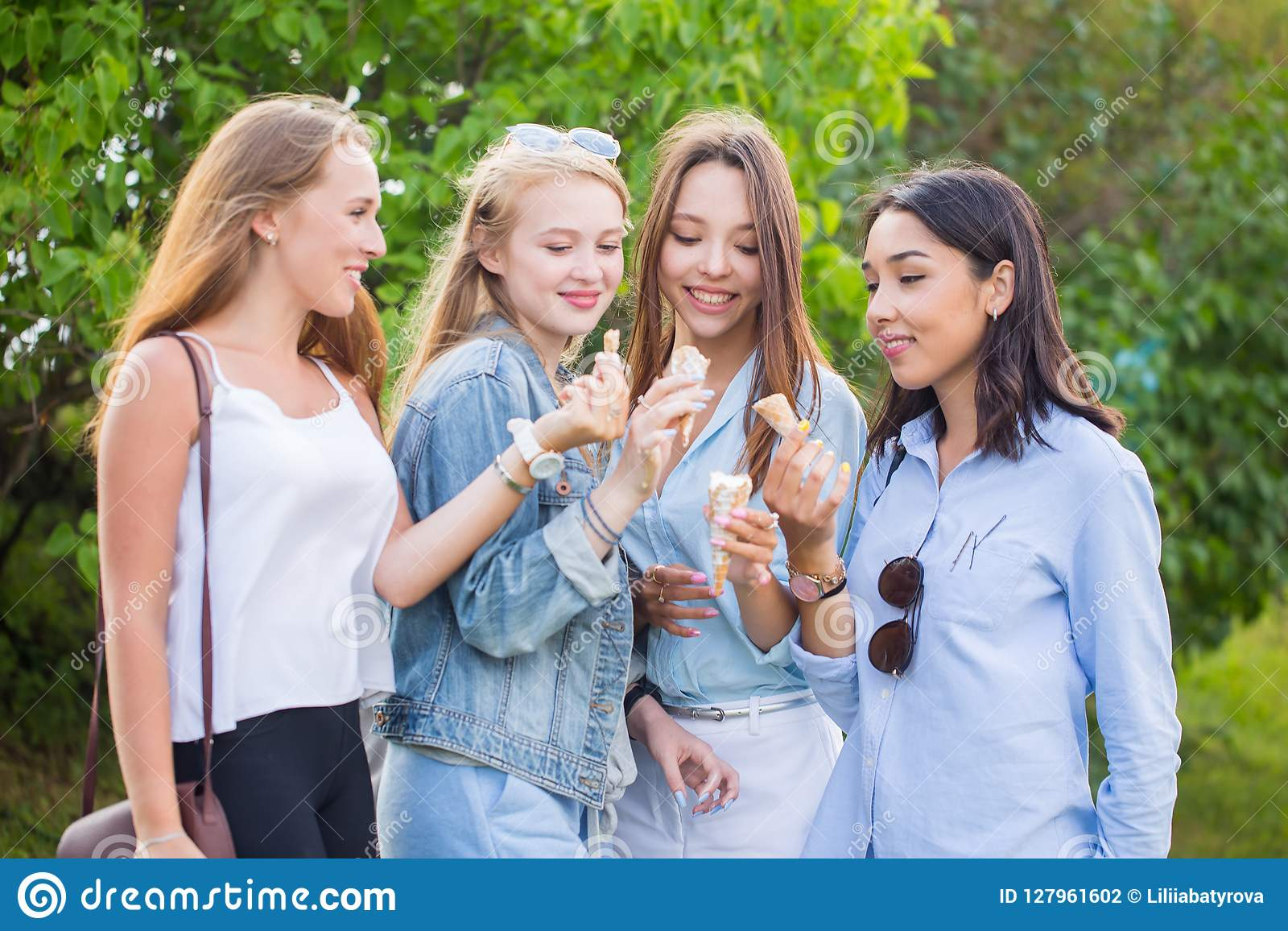 Four young joyful student girls laughing and eating ice cream in the Park, outdoors