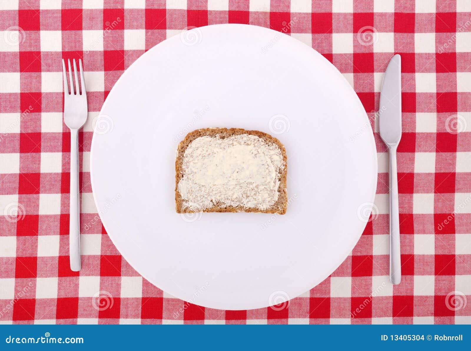 Fourchette, couteau et une part de pain beurrée