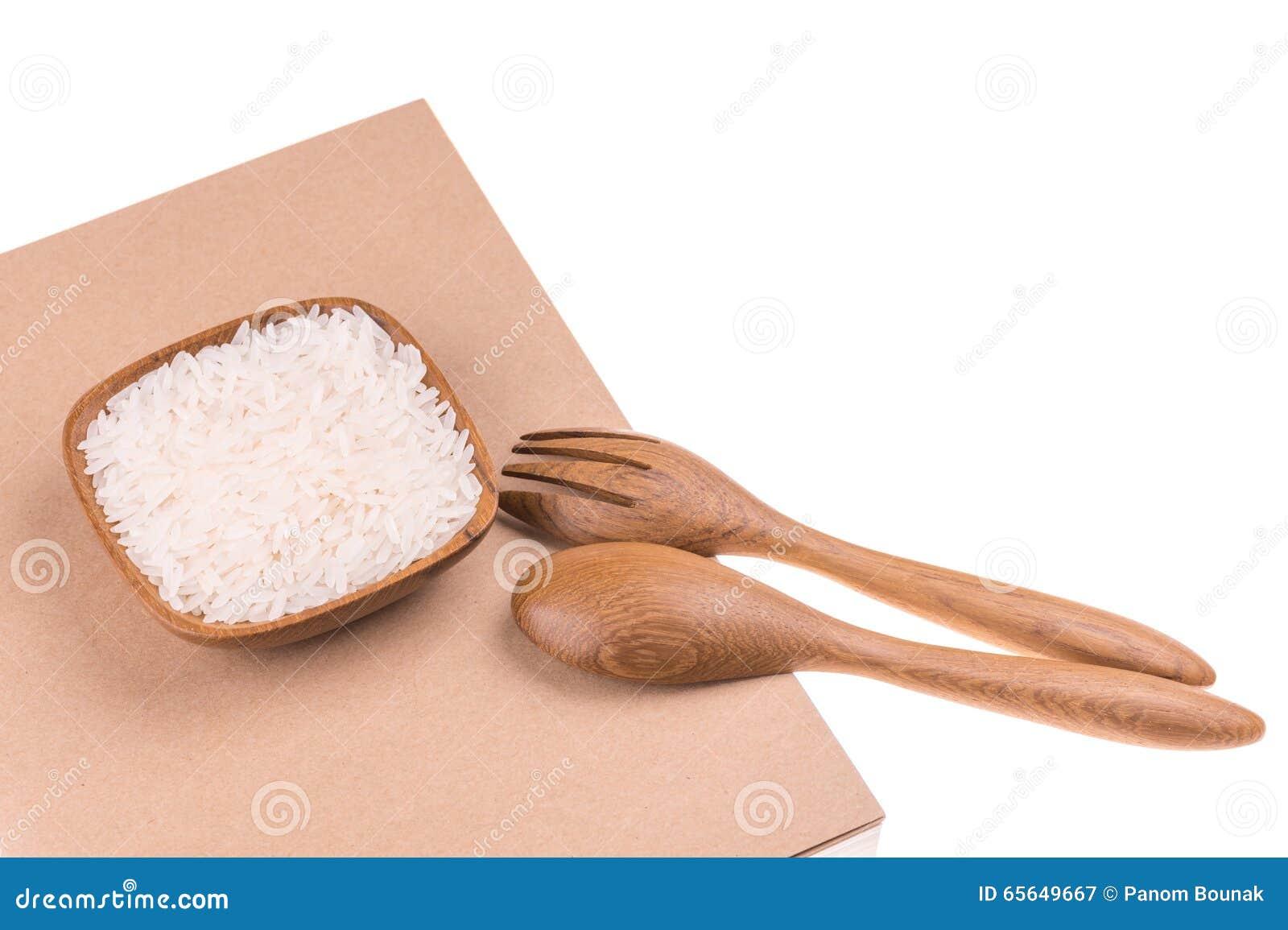 Fourchette et cuillère en bois avec du riz dans la petite cuvette en bois sur le carnet