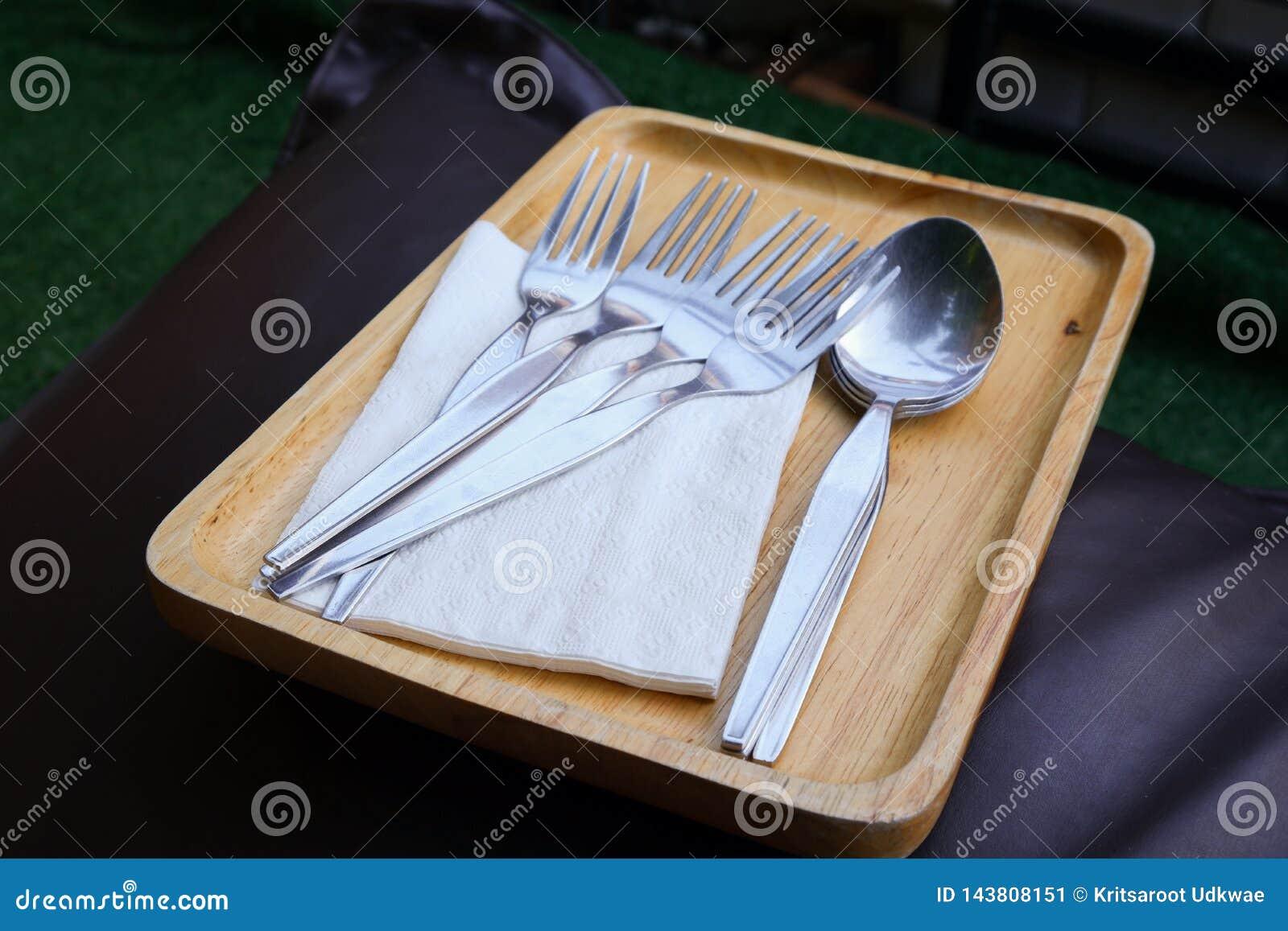 Fourchettes, cuillères, et papiers de soie de soie sur le plateau en bois