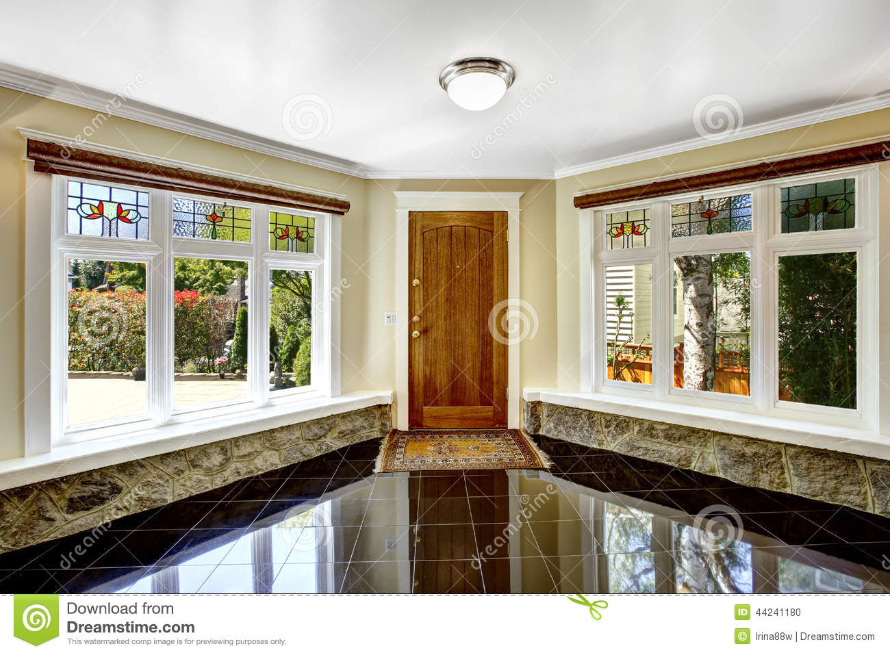 Large Foyer Window : Foyer with black shiny tile floor and stone trim under the