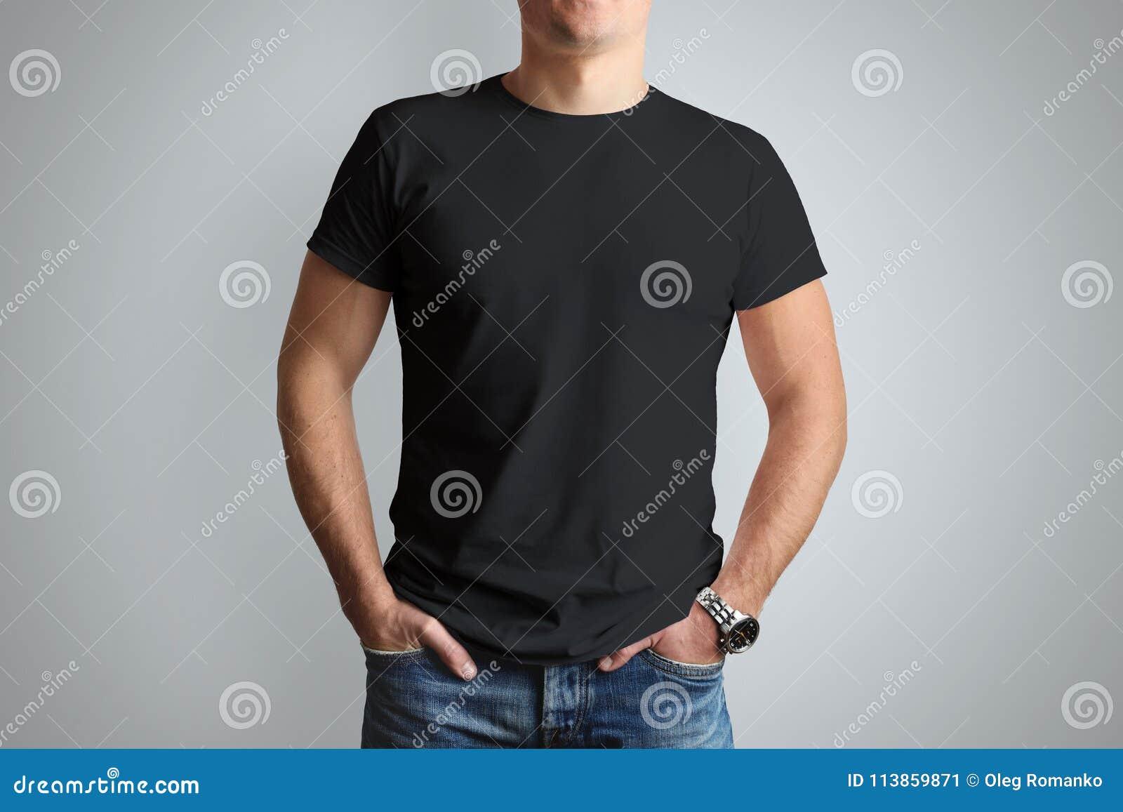 Främre modellsvartT-tröja på en ung grabb som isoleras på gråa lodisar