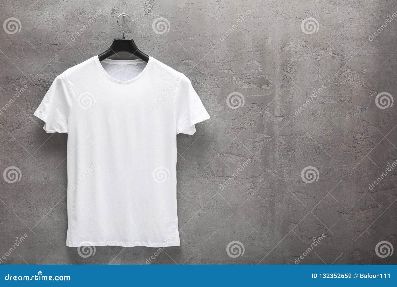 Främre sida av den manliga vita bomullst-skjortan på en hängare
