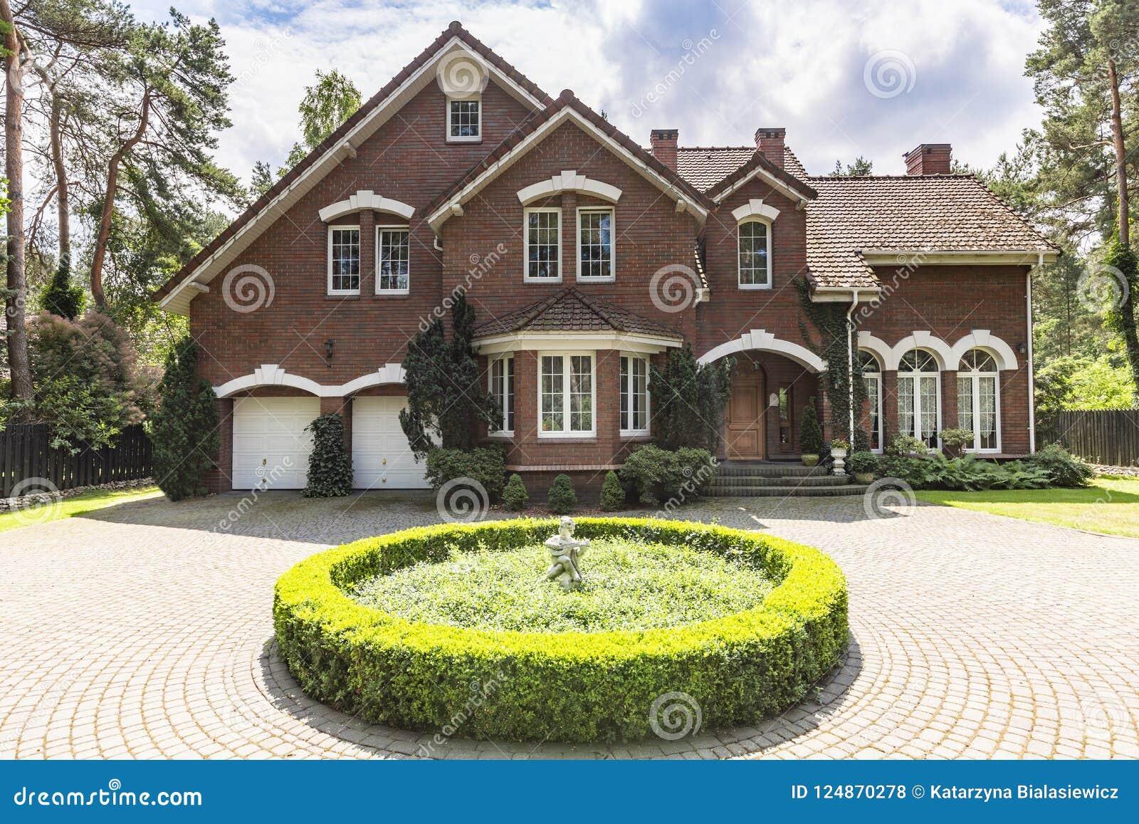 Främre sikt av för engelskastil för röd tegelsten ett klassiskt hus med en ste